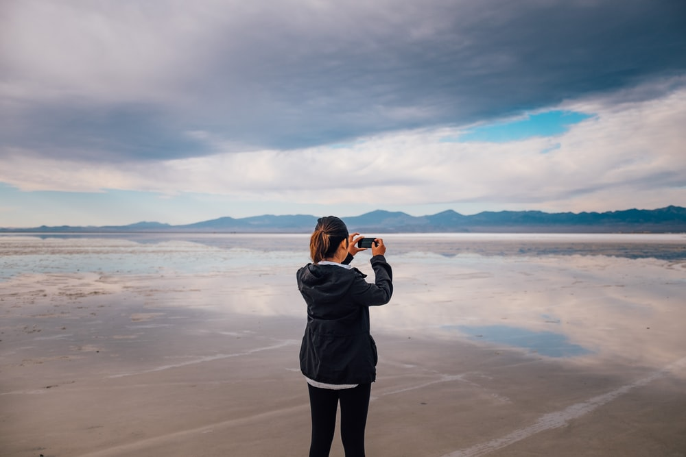 woman in gray jacket standing on beach during daytime