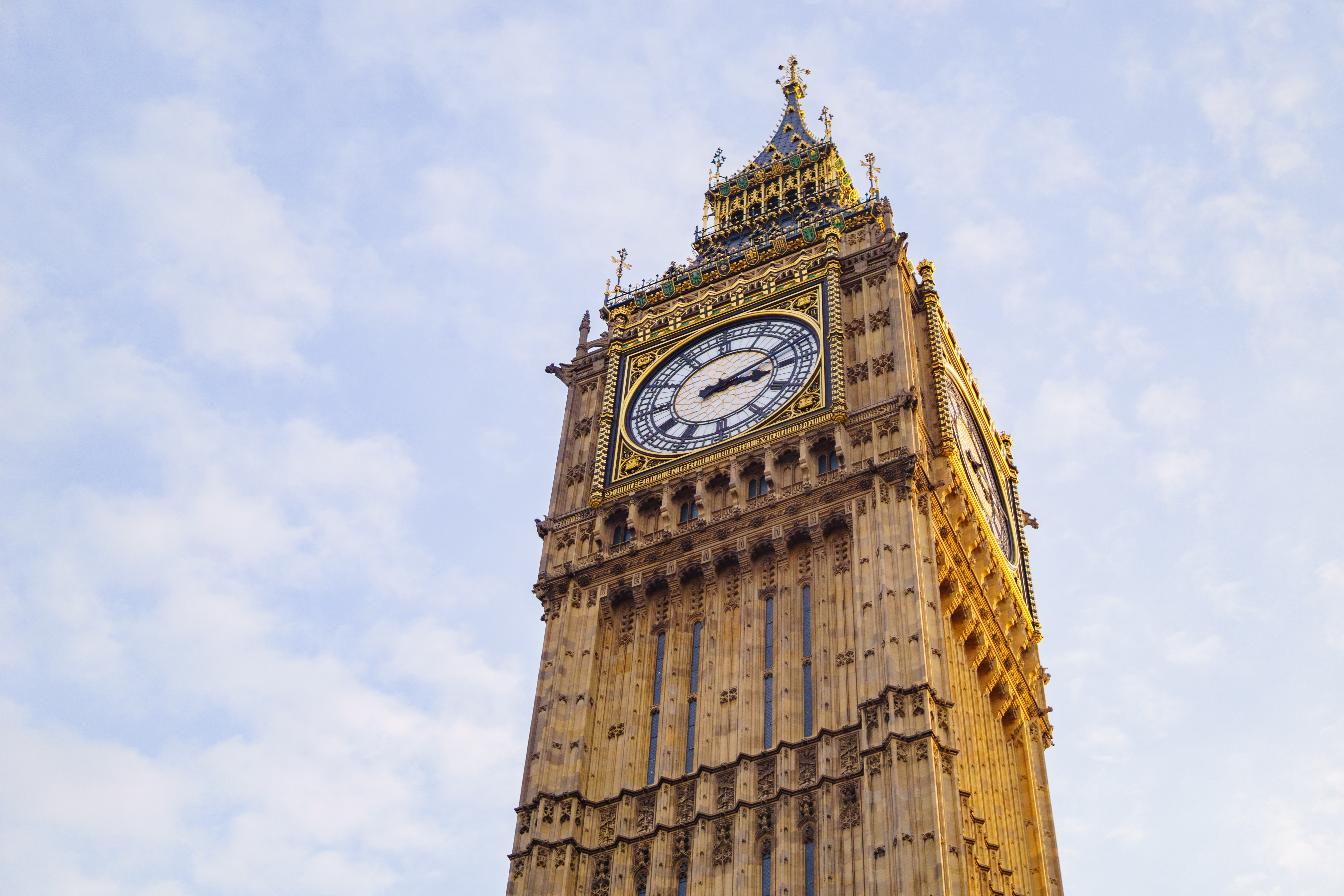 Big Ben clock tower in London with a blue sky and white clouds