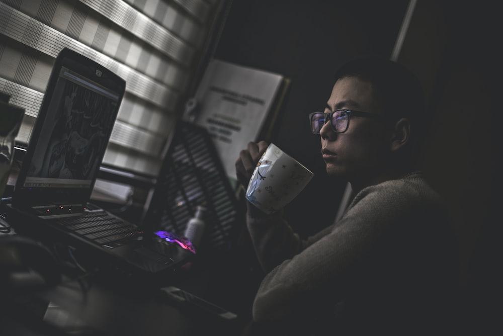 man holding mug in front laptop computer