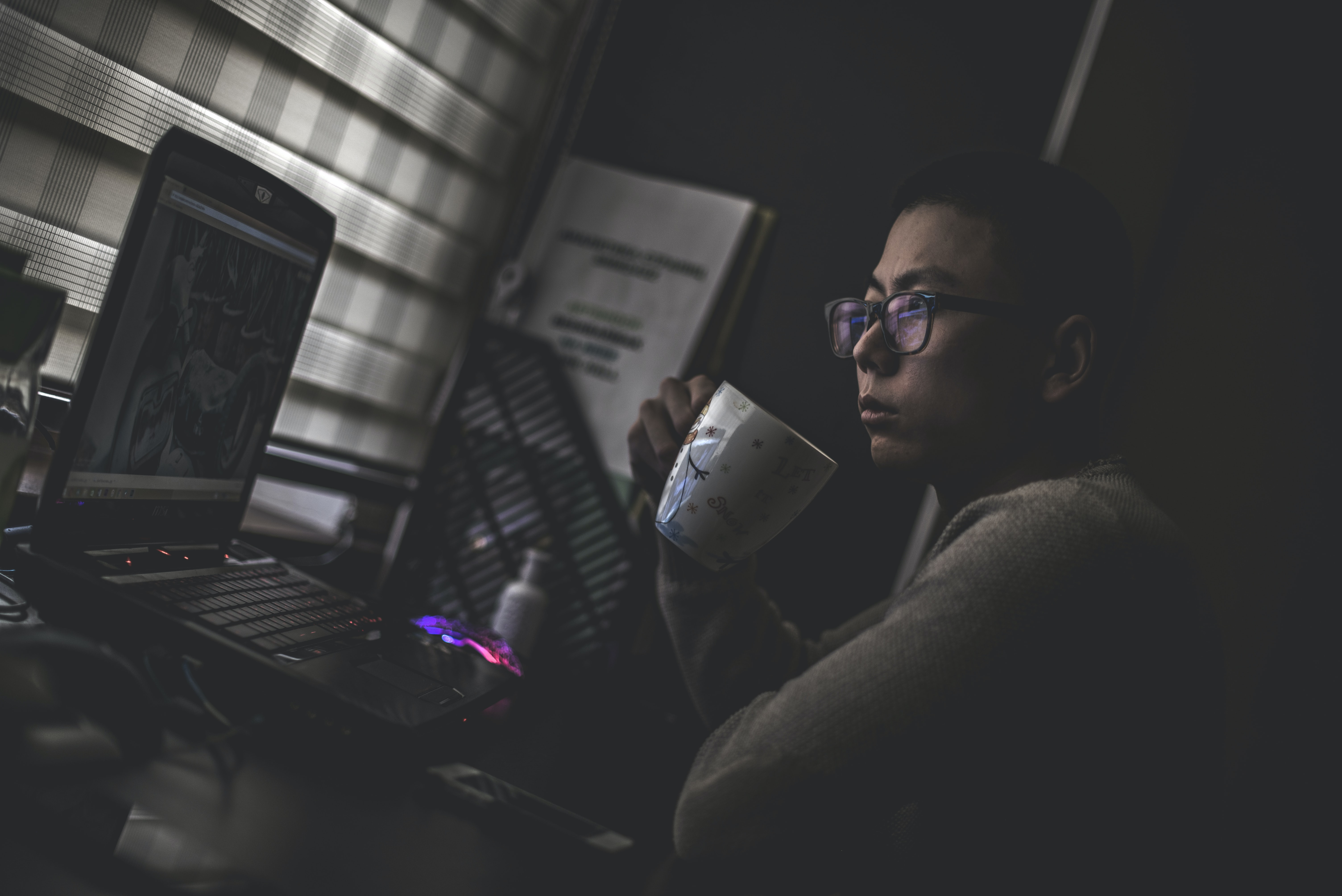 man holding mug in front laptop computer