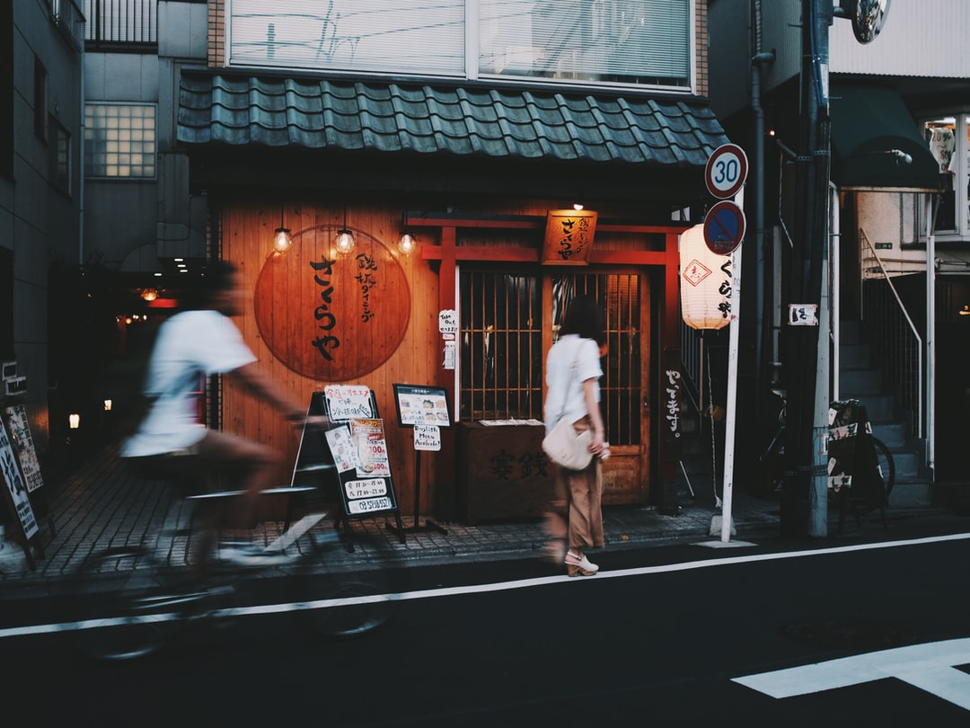 A woman walks past a small wooden shop as a cyclist speeds by