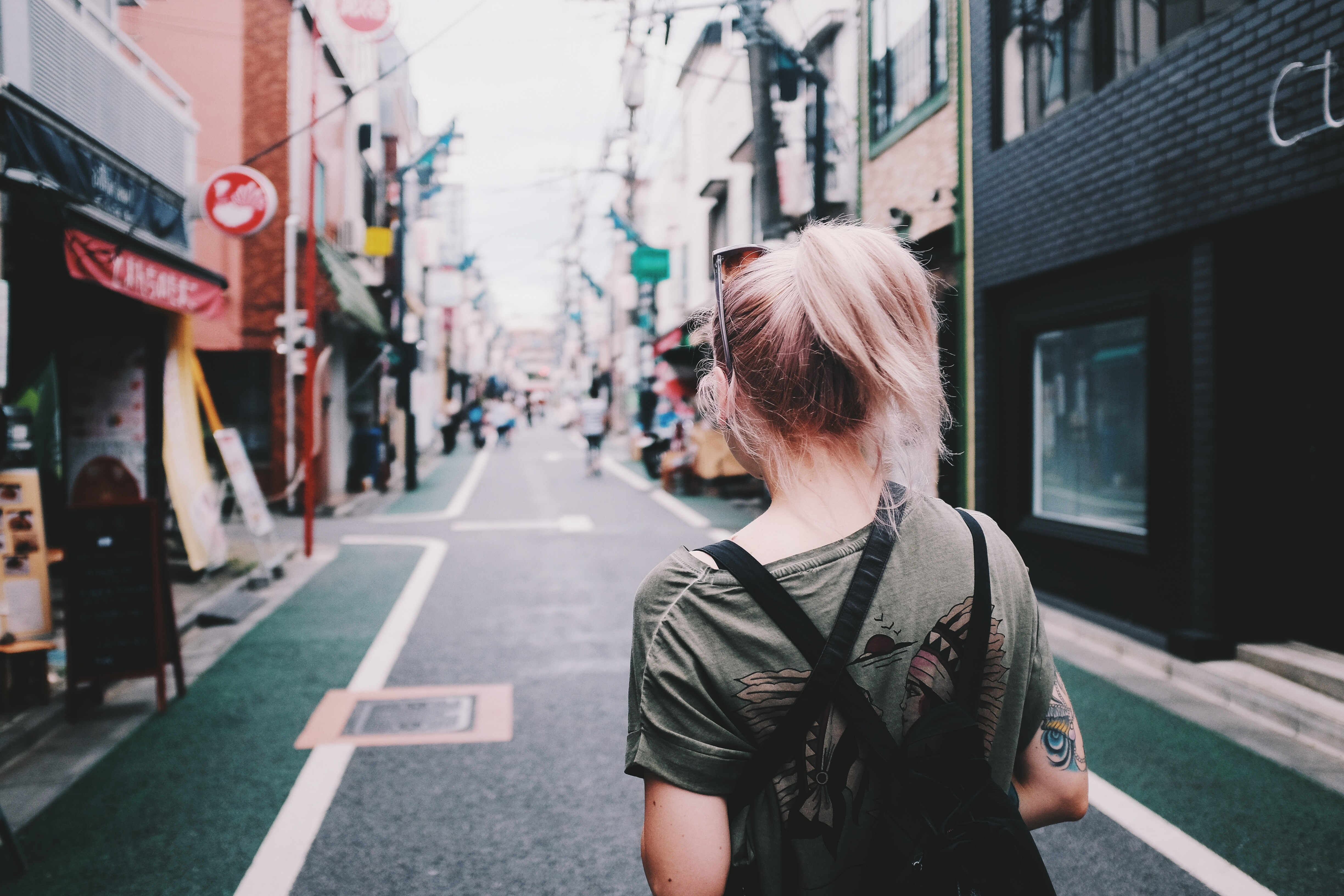 A woman in a ponytail and t-shirt walks down a street by shops in Shimo-kitazawa Station