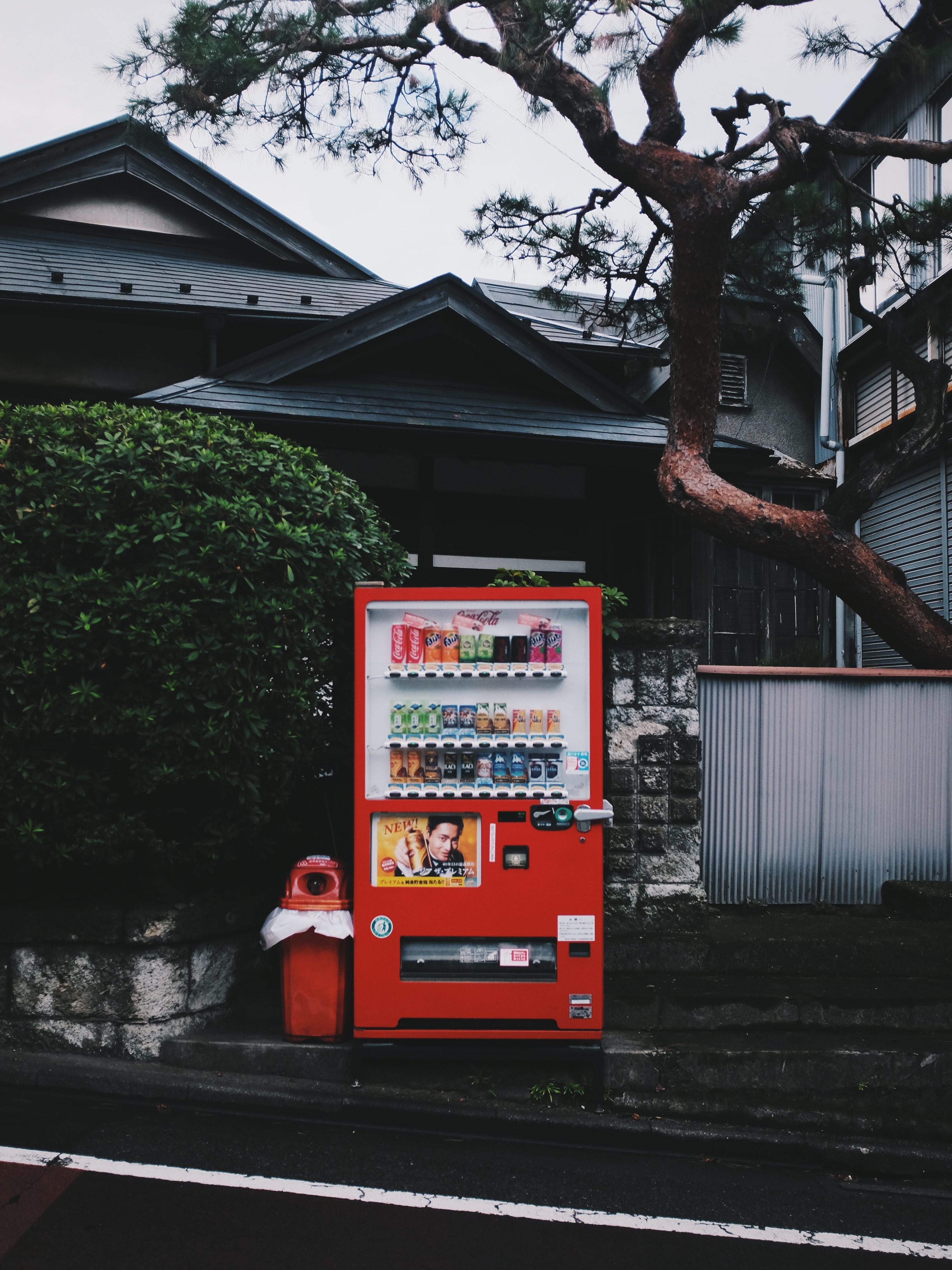 red vending machine beside red plastic trash can