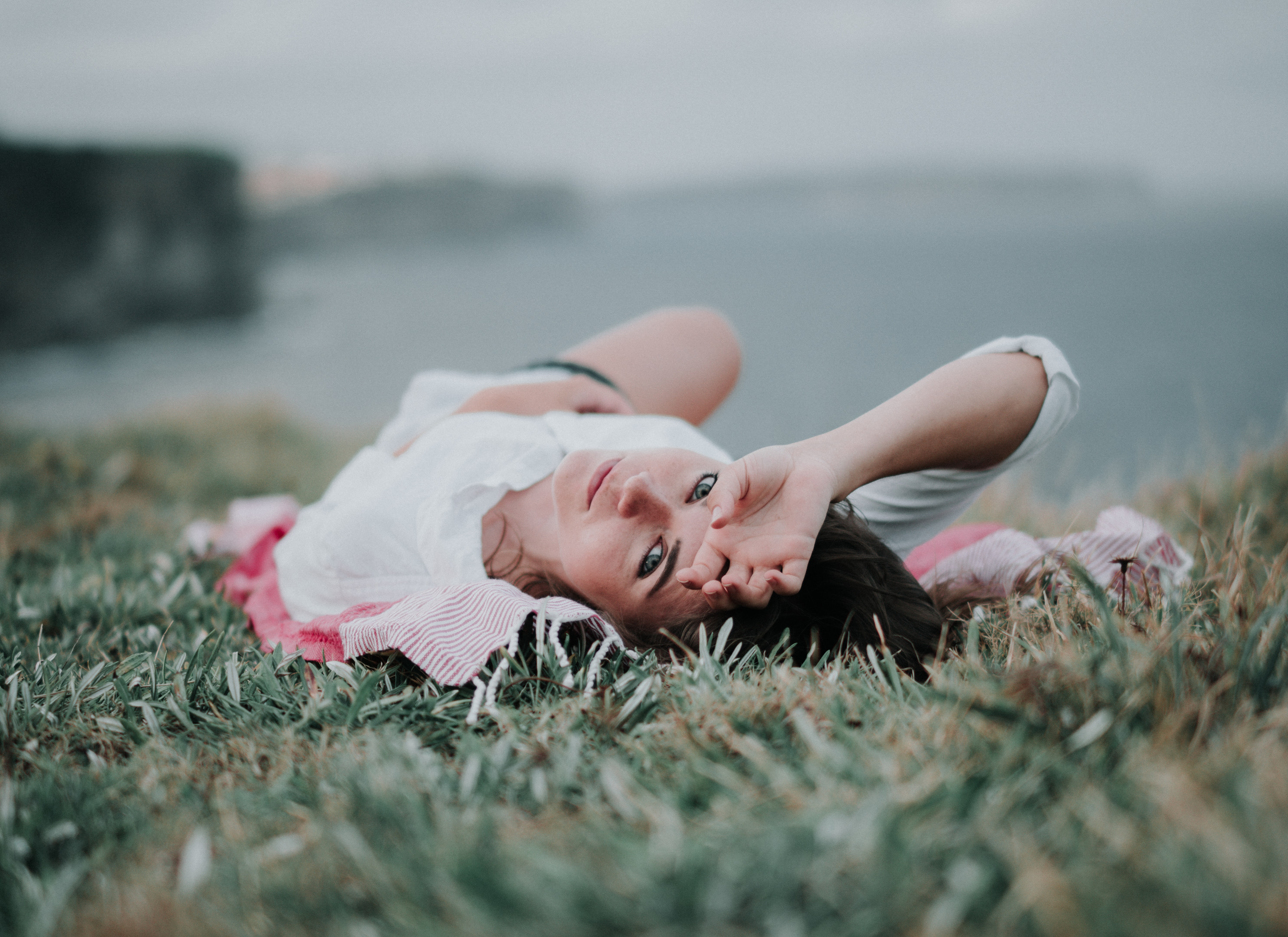 Woman lying in the grass looking at the camera at Bondi Beach