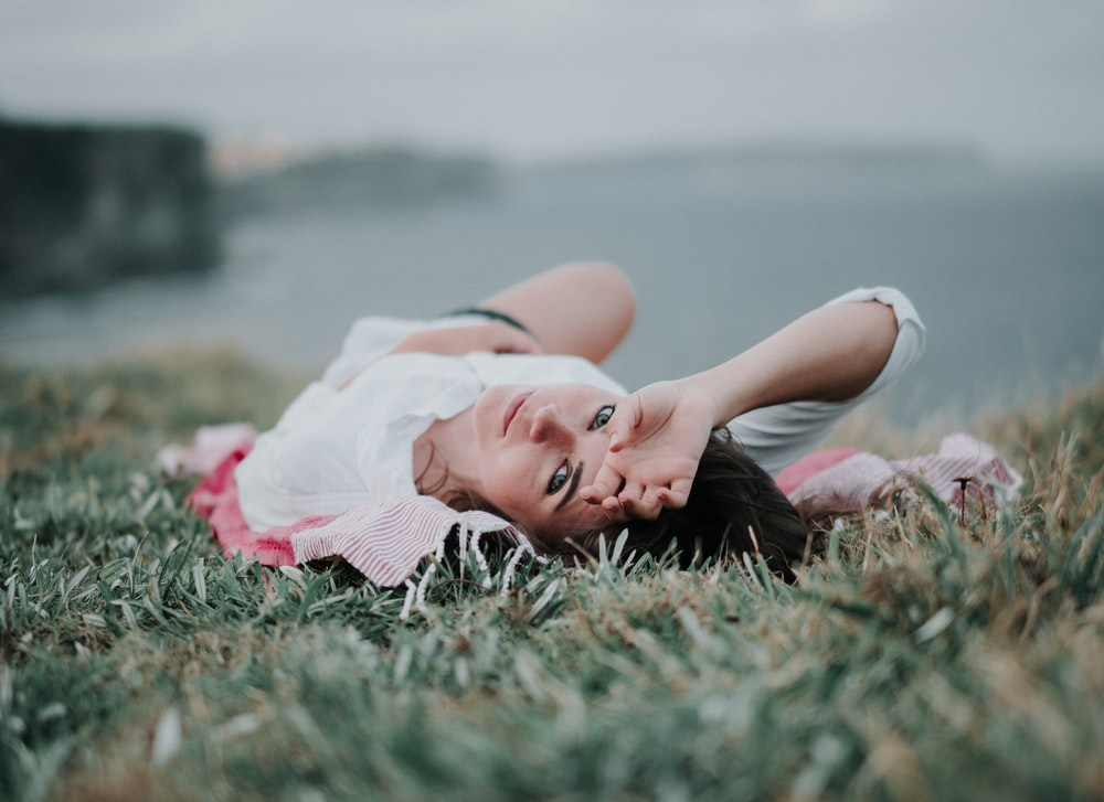 selective focus of woman lying on green grass