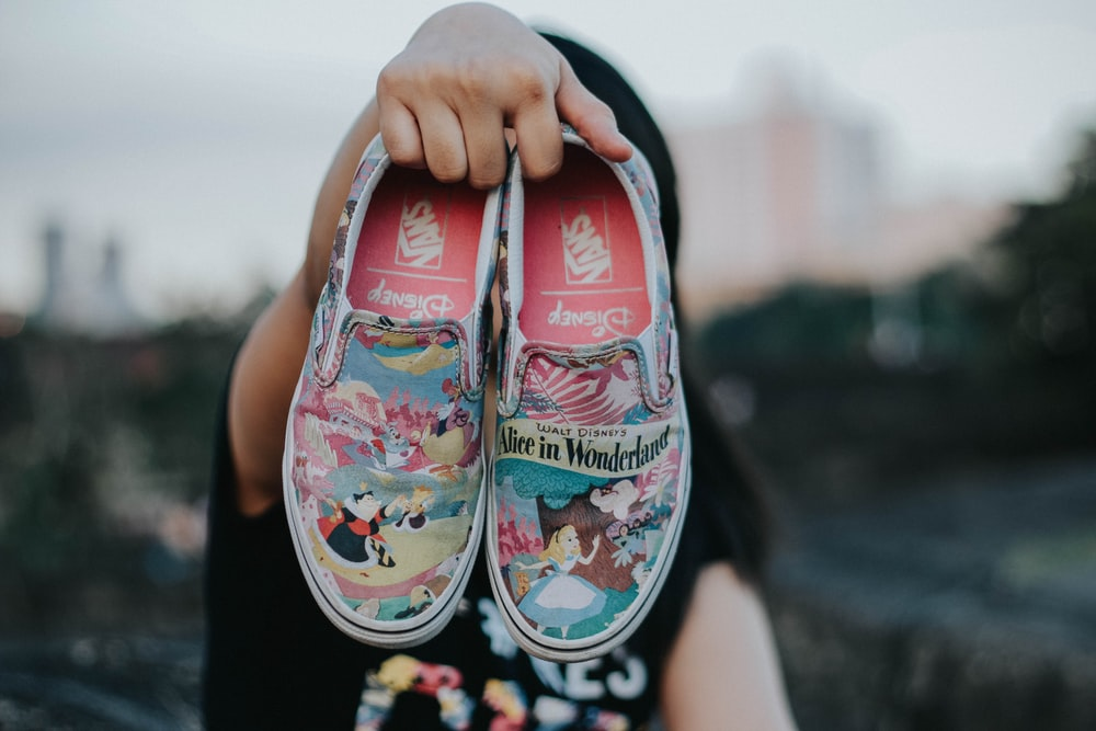 tilt shift lens photography of Vans Alice in Wonderland slip-on shoes