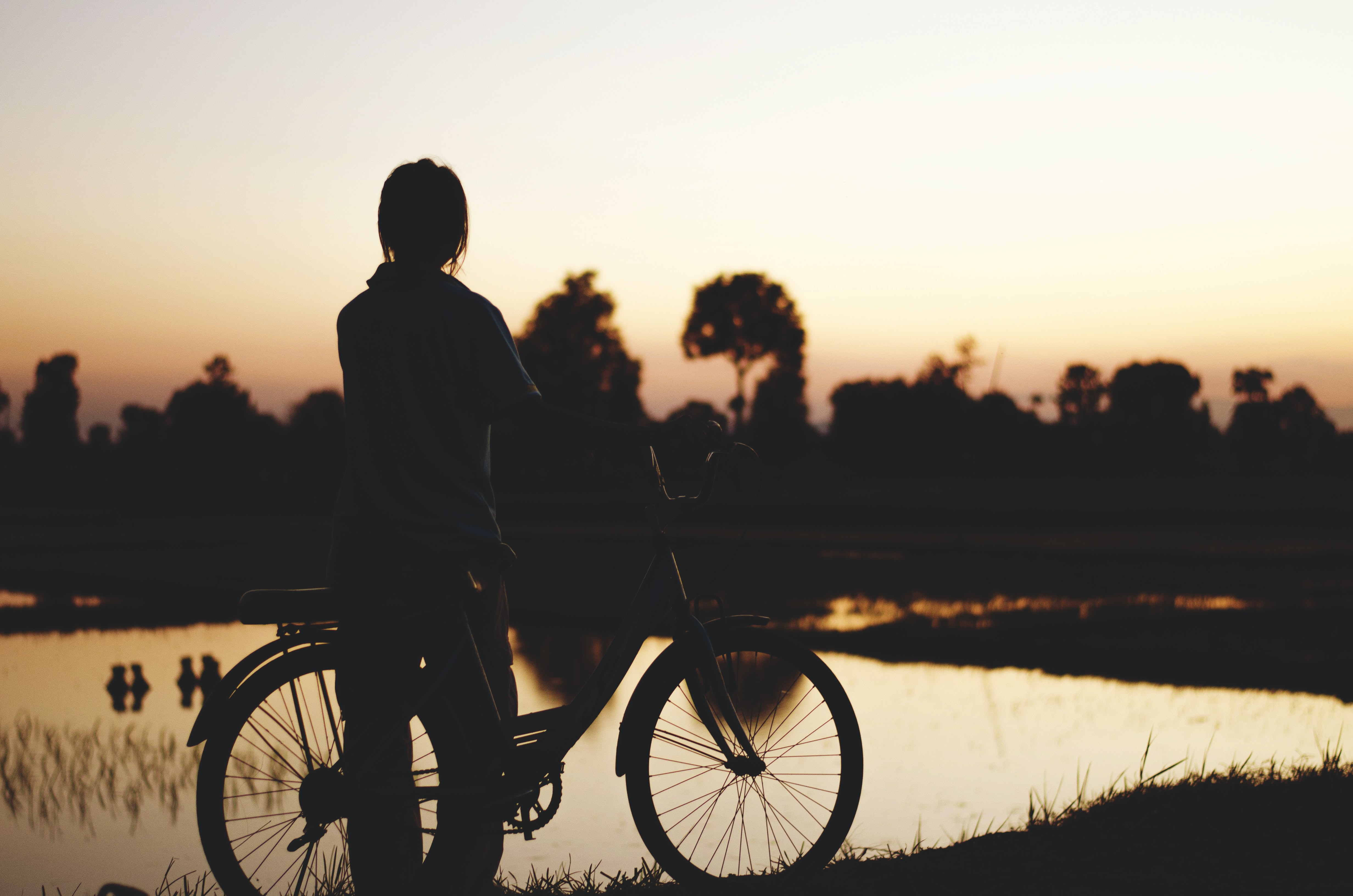 A person in silhouette stands next to a bicycle by a lake at sunset