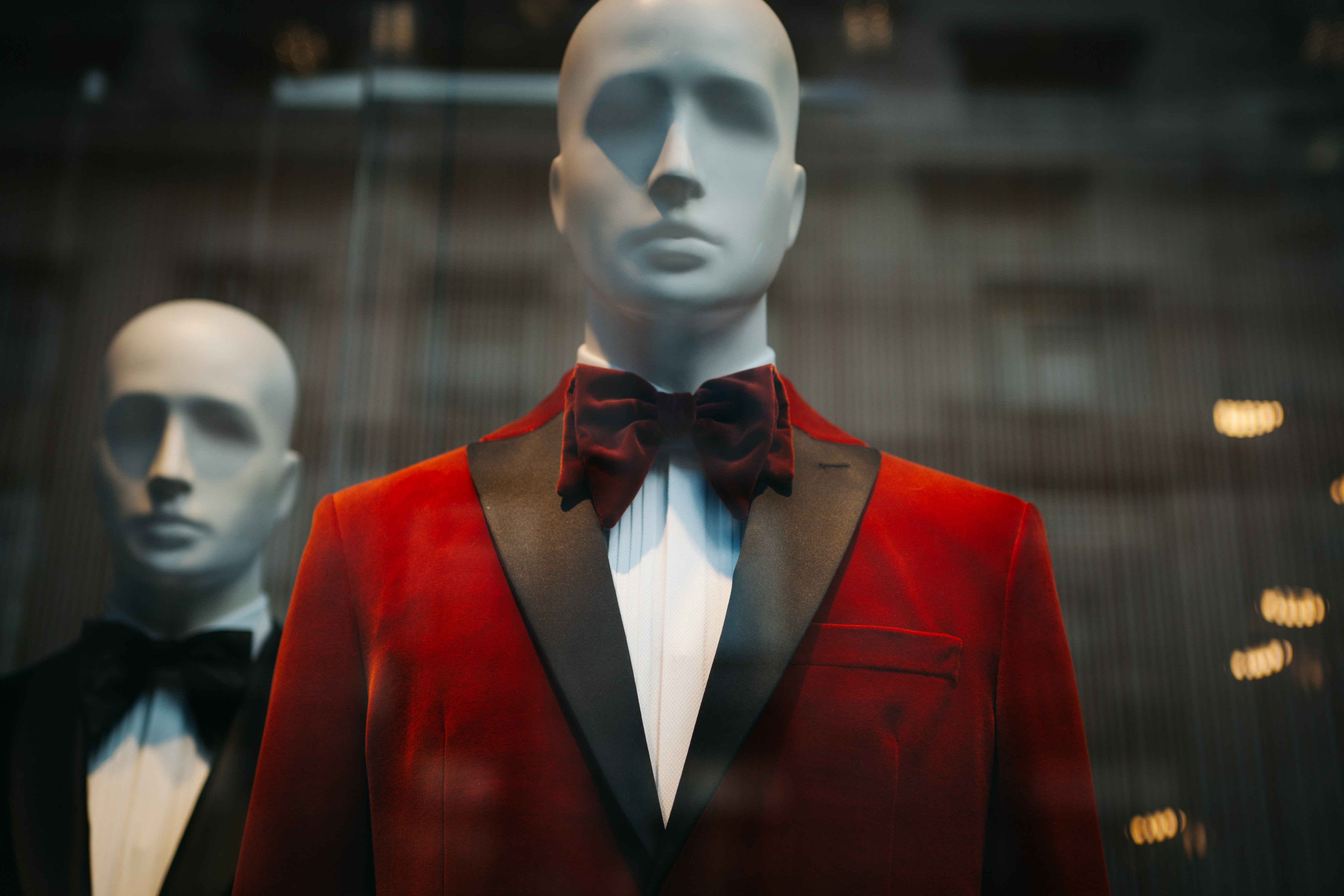 Store mannequins in fashionable tuxedos in a shop window