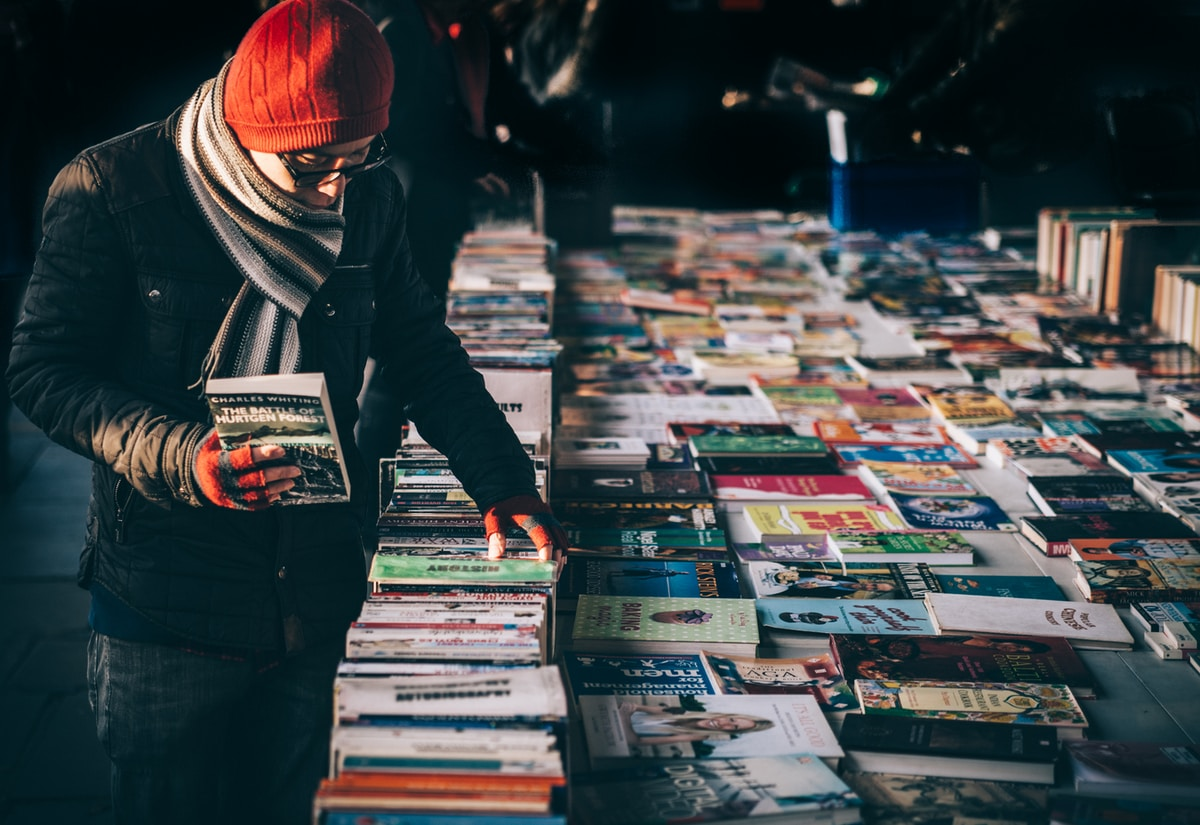 A person wearting a red beanie, striped grey scarf, black jacket, dark blue jeans, and red fingerless gloves perusing a  table filled with books.  They selected The Battle of Hurtgen Forest by Charles Whiting and are looking at another history book.