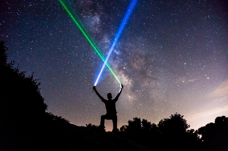 man holding green and blue flashlights