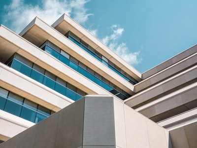 low angle photo of beige concrete building under cloudy sky building teams background
