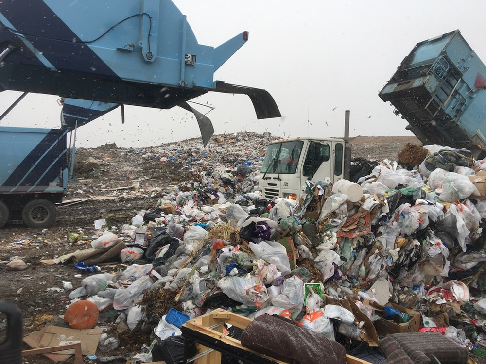 Bags of garbage getting emptied from trucks at a dump.