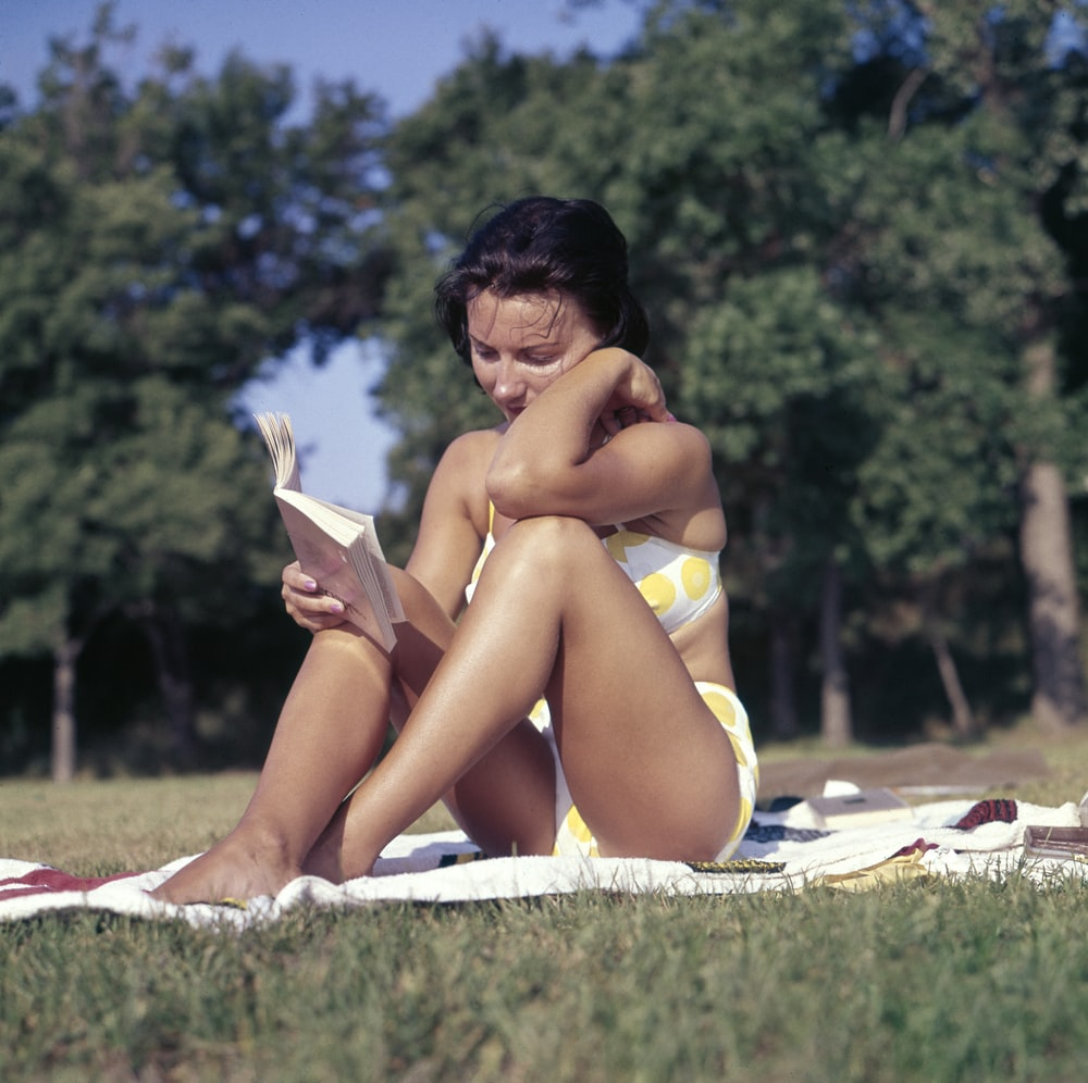 woman sitting on mat reading book