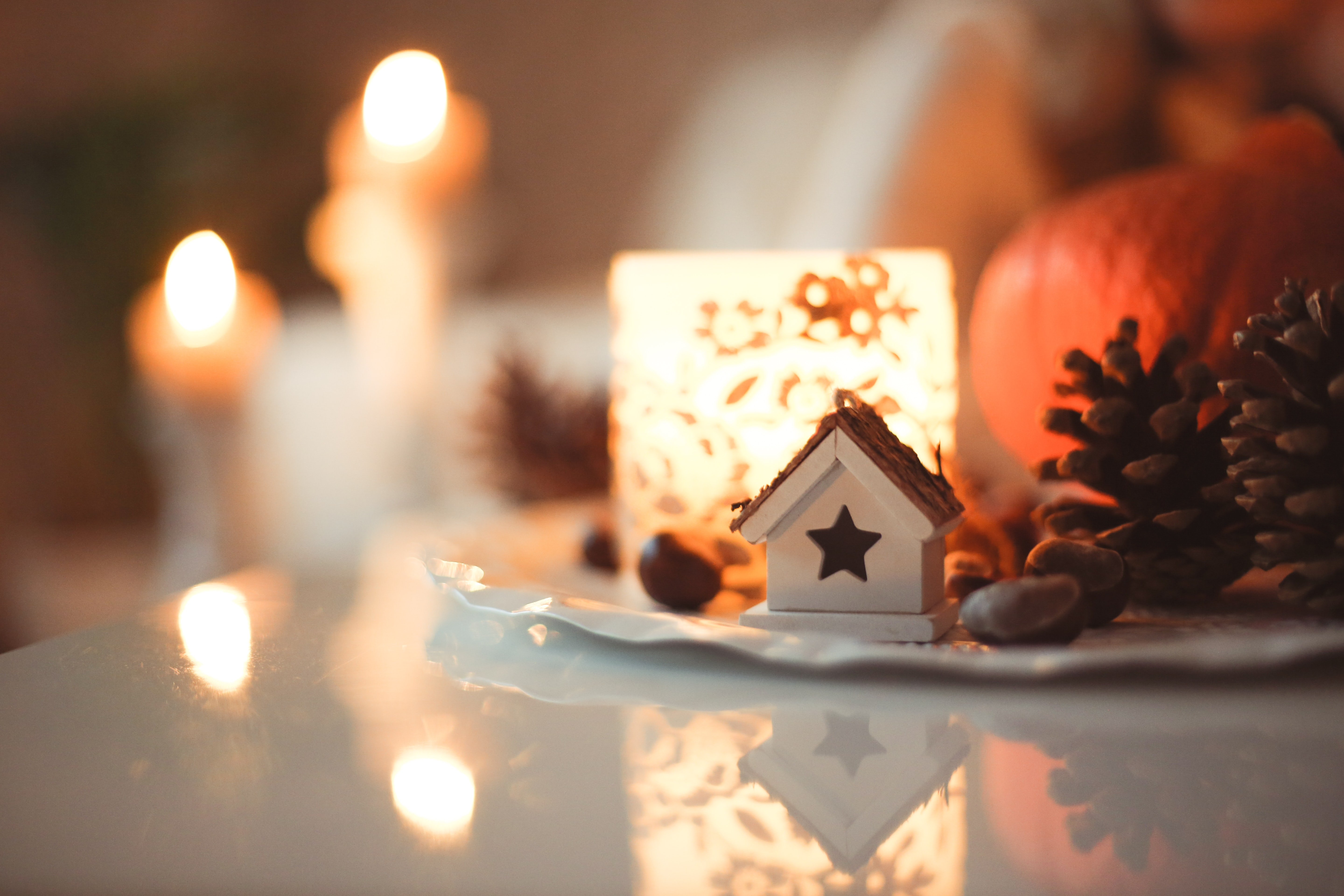 A macro view of a festive Christmas ornament on a table with candles blurrily lit in the background.