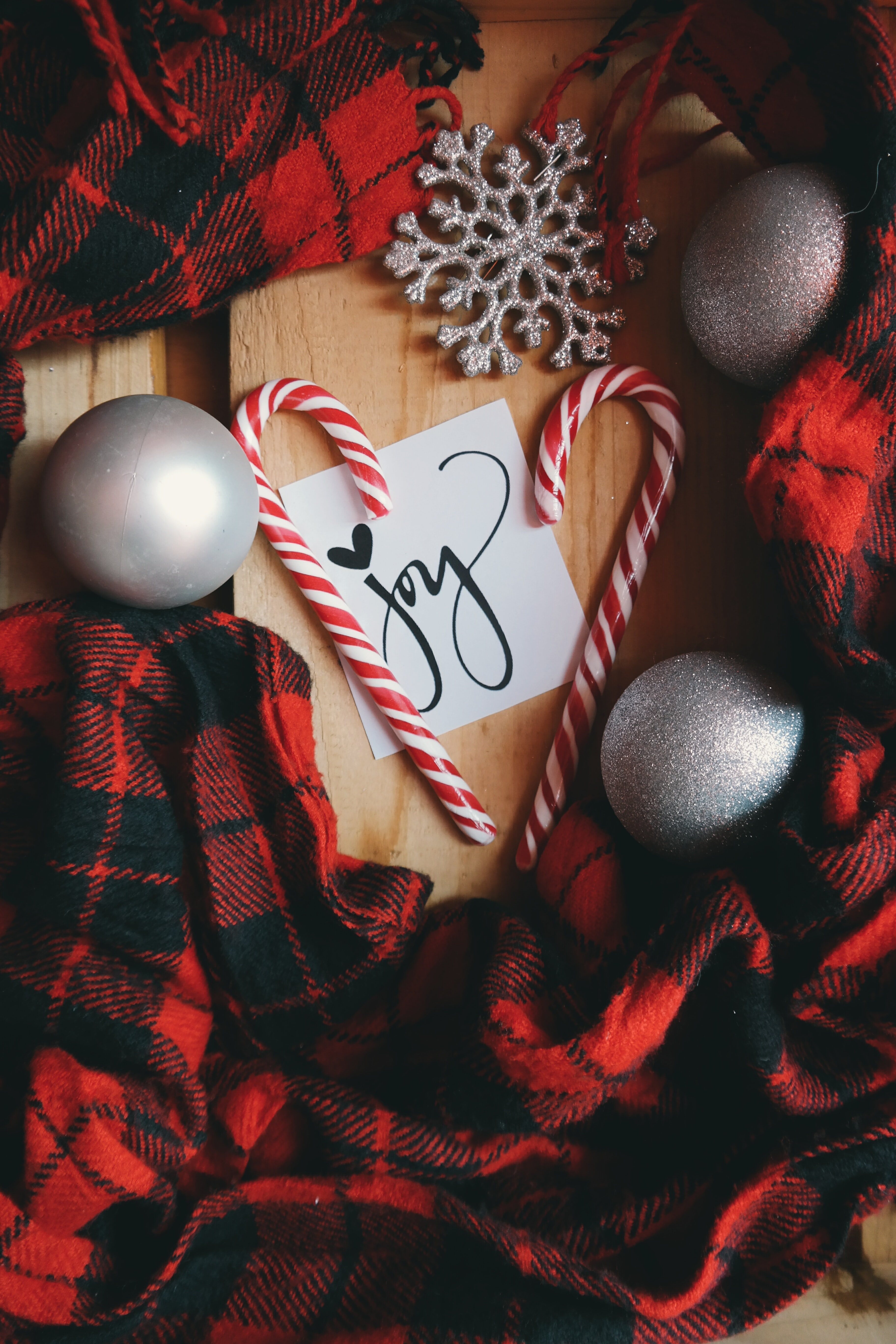 """A white note that says """"Joy,"""" surrounded by candy canes, XMAS ornaments and red plaid material."""