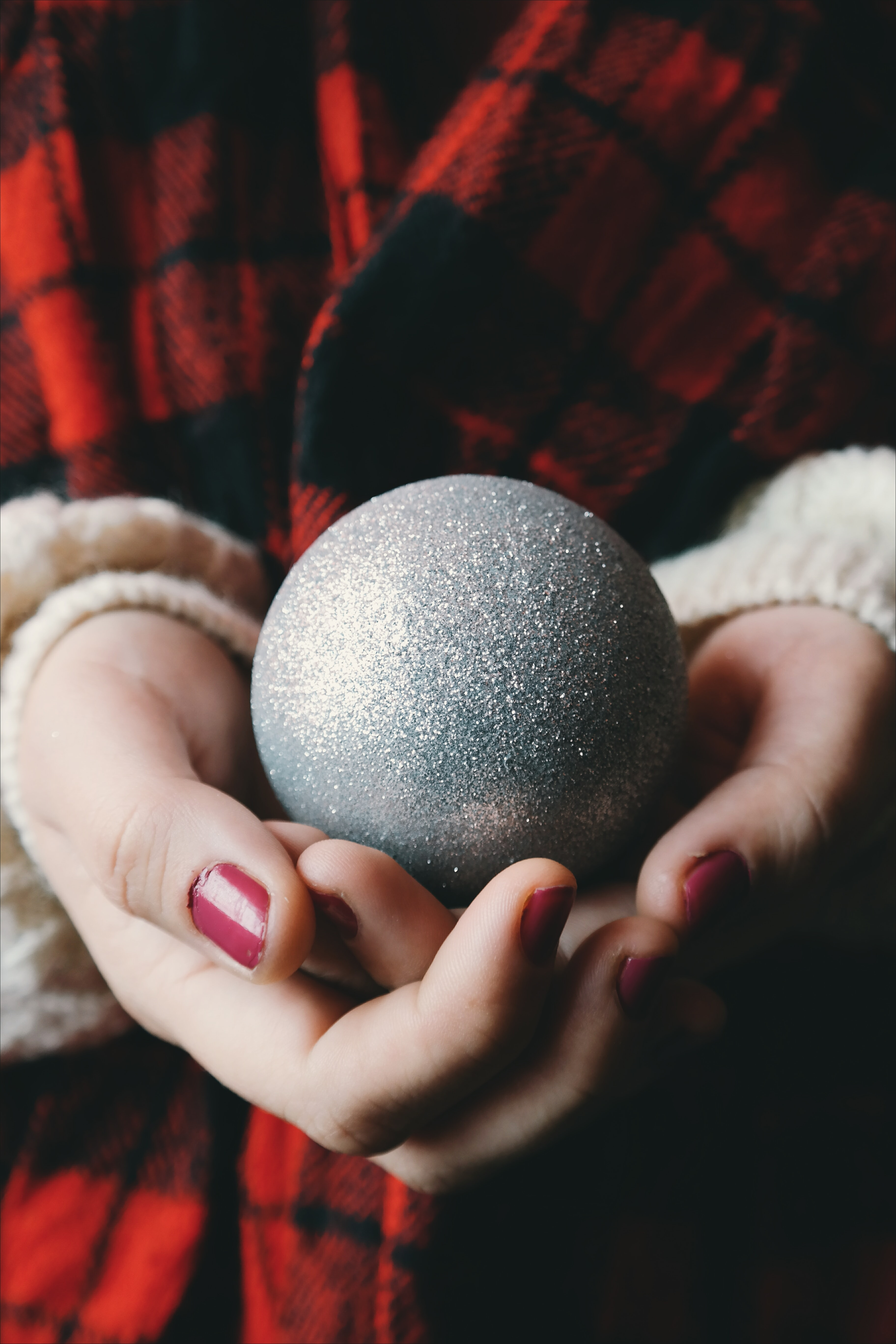 A woman with red painted nails holding a silver Christmas ornament.