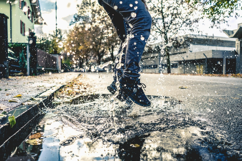 person making splash on water puddle on road