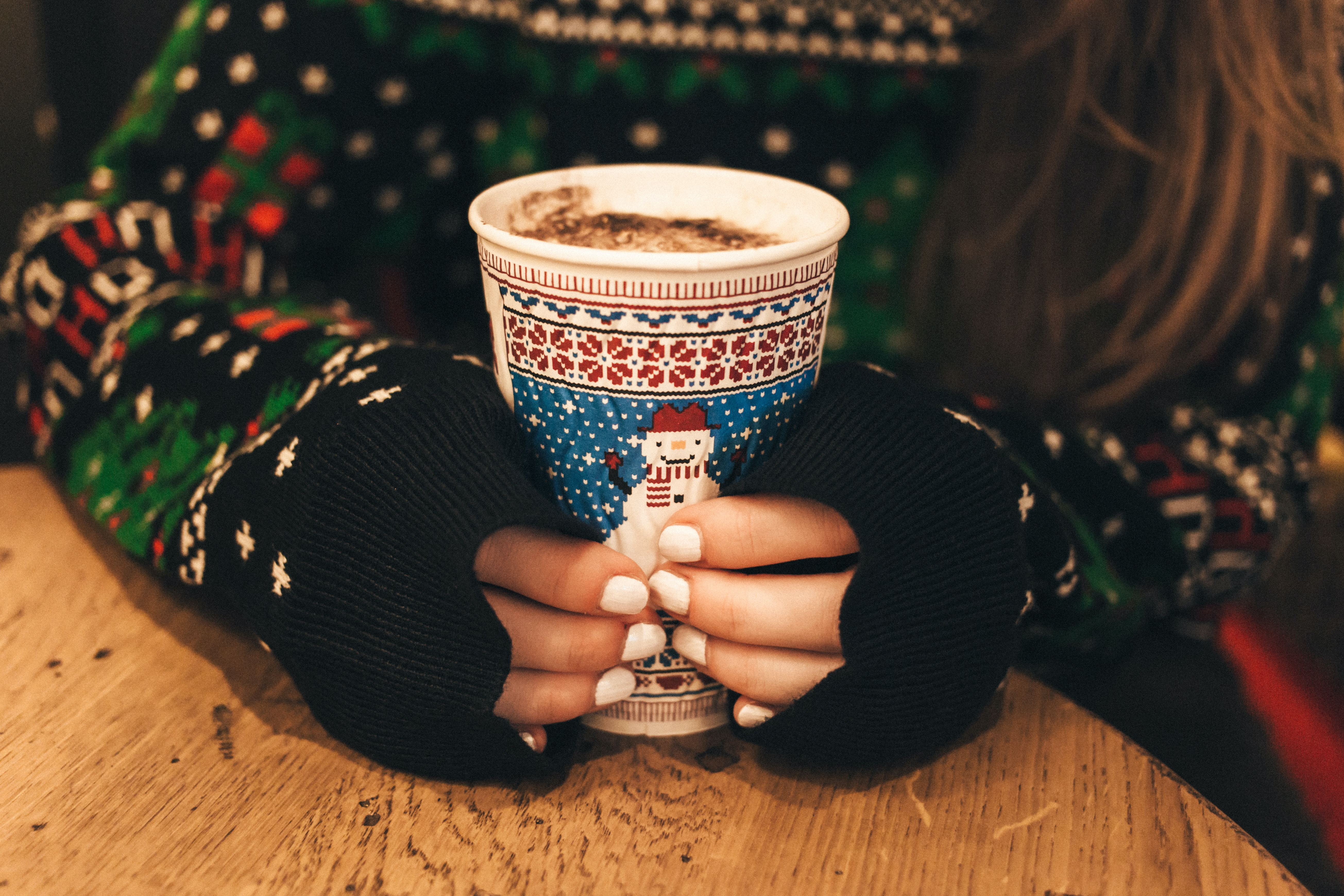 A long-haired woman with white painted nails holding a cup of hot chocolate.