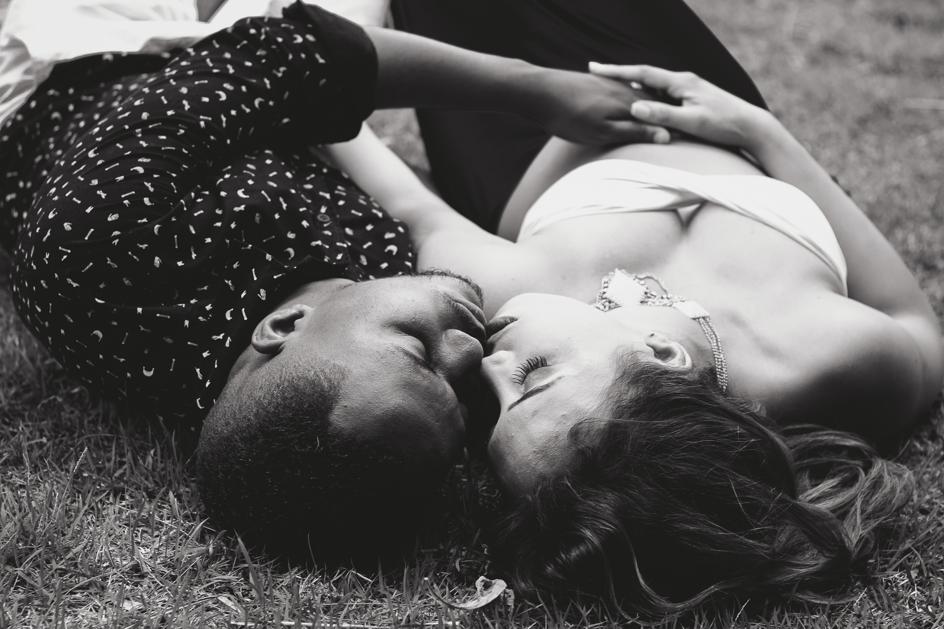 A man and a woman lying down on grass cuddle and kiss in black-and-white