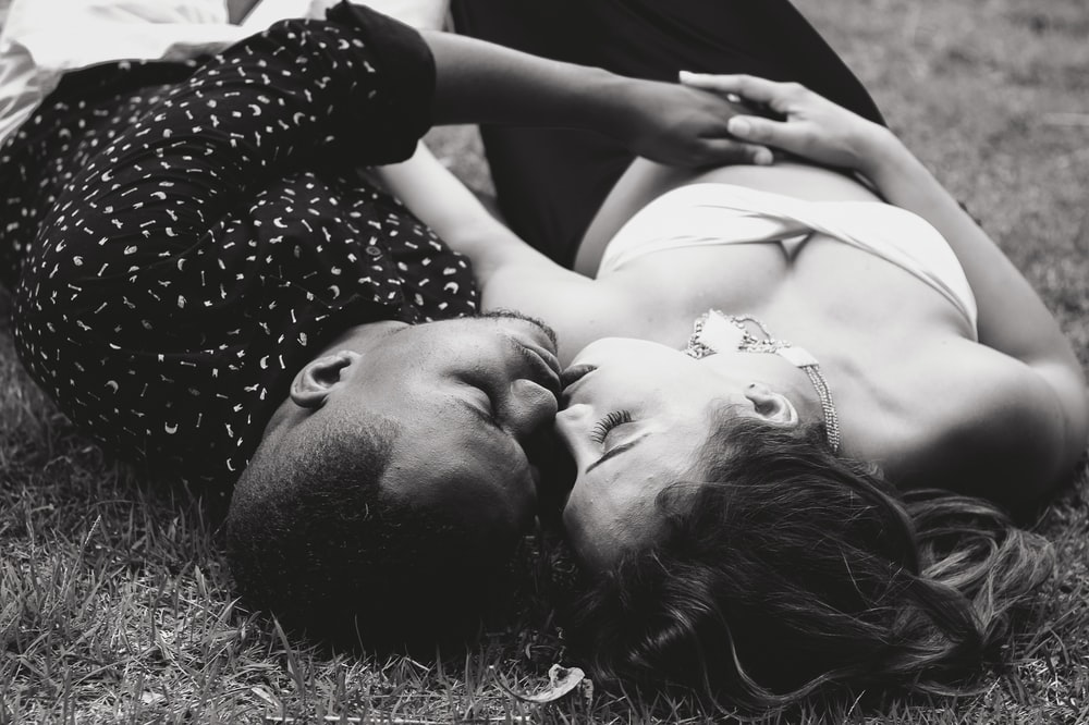 grayscale photo of man and woman facing each other and lying on grass