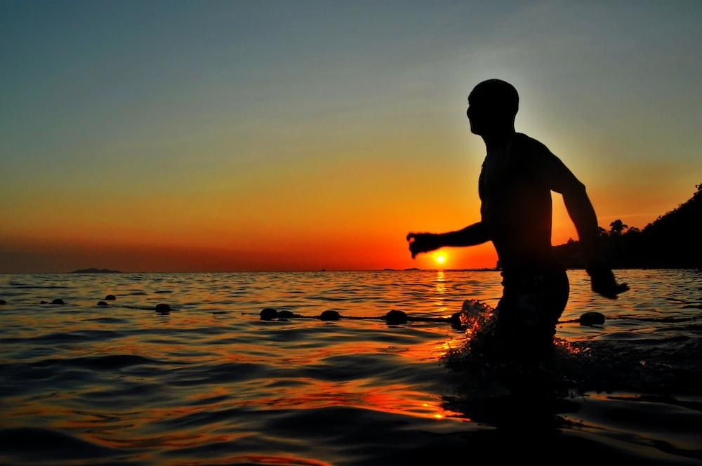 silhouette of man walking in body of water