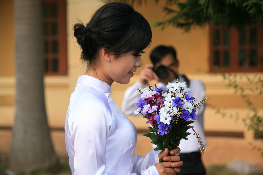 woman holding assorted-color flower bouquet