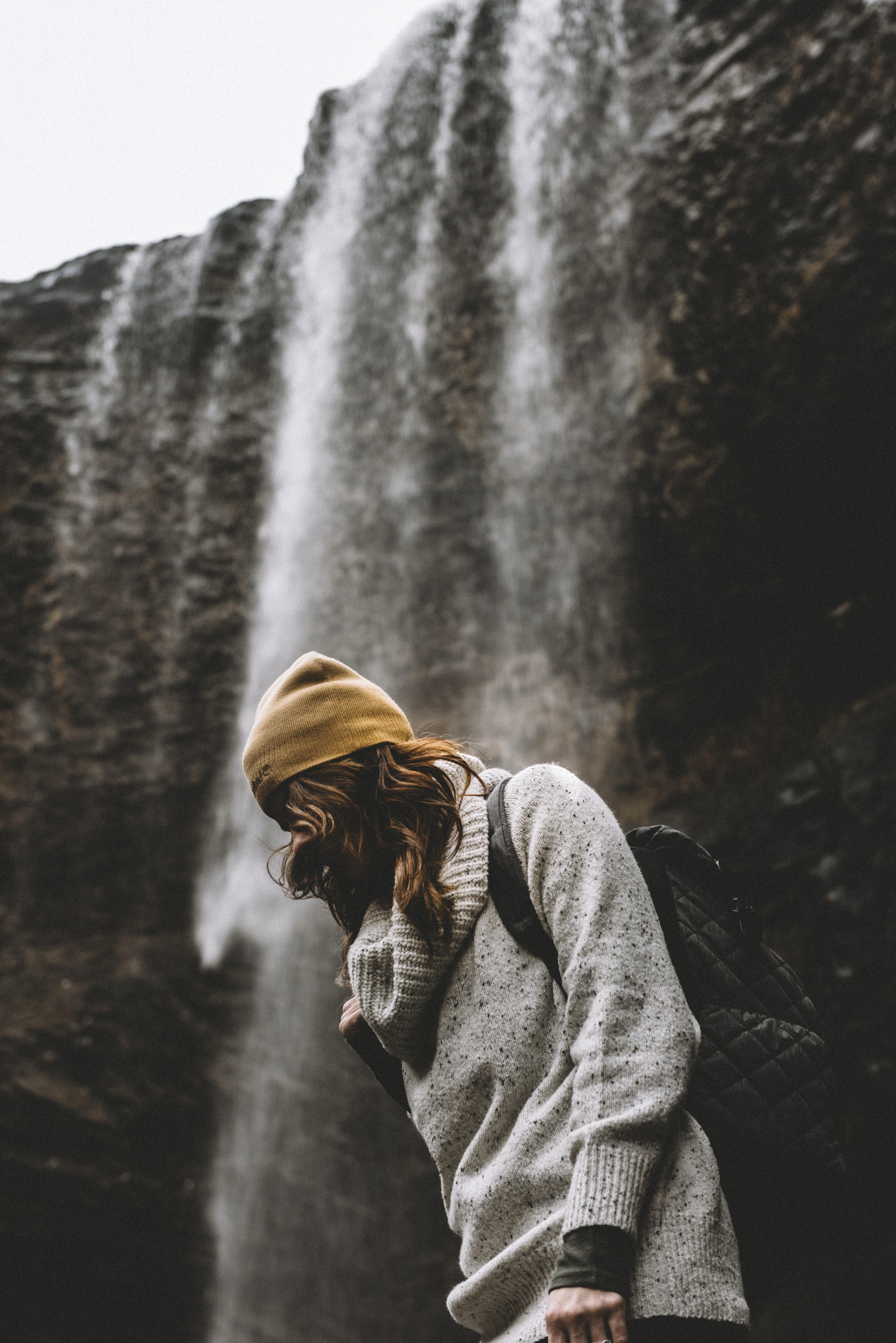 Hiker wearing a backpack walking past a waterfall