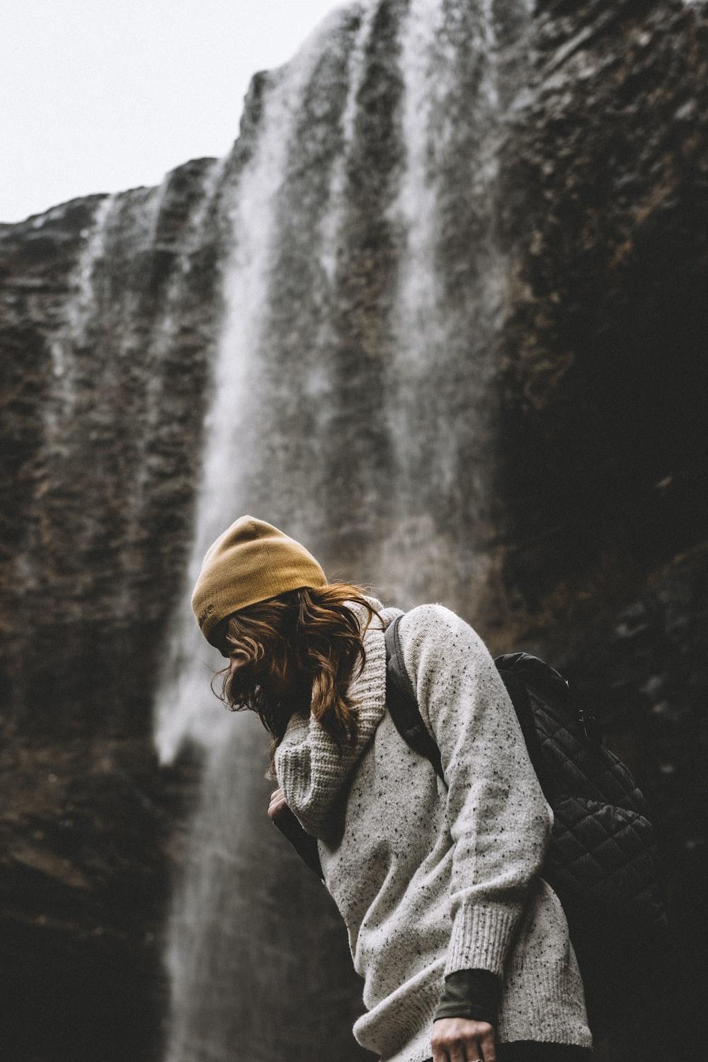 woman in knit cap standing near waterfalls