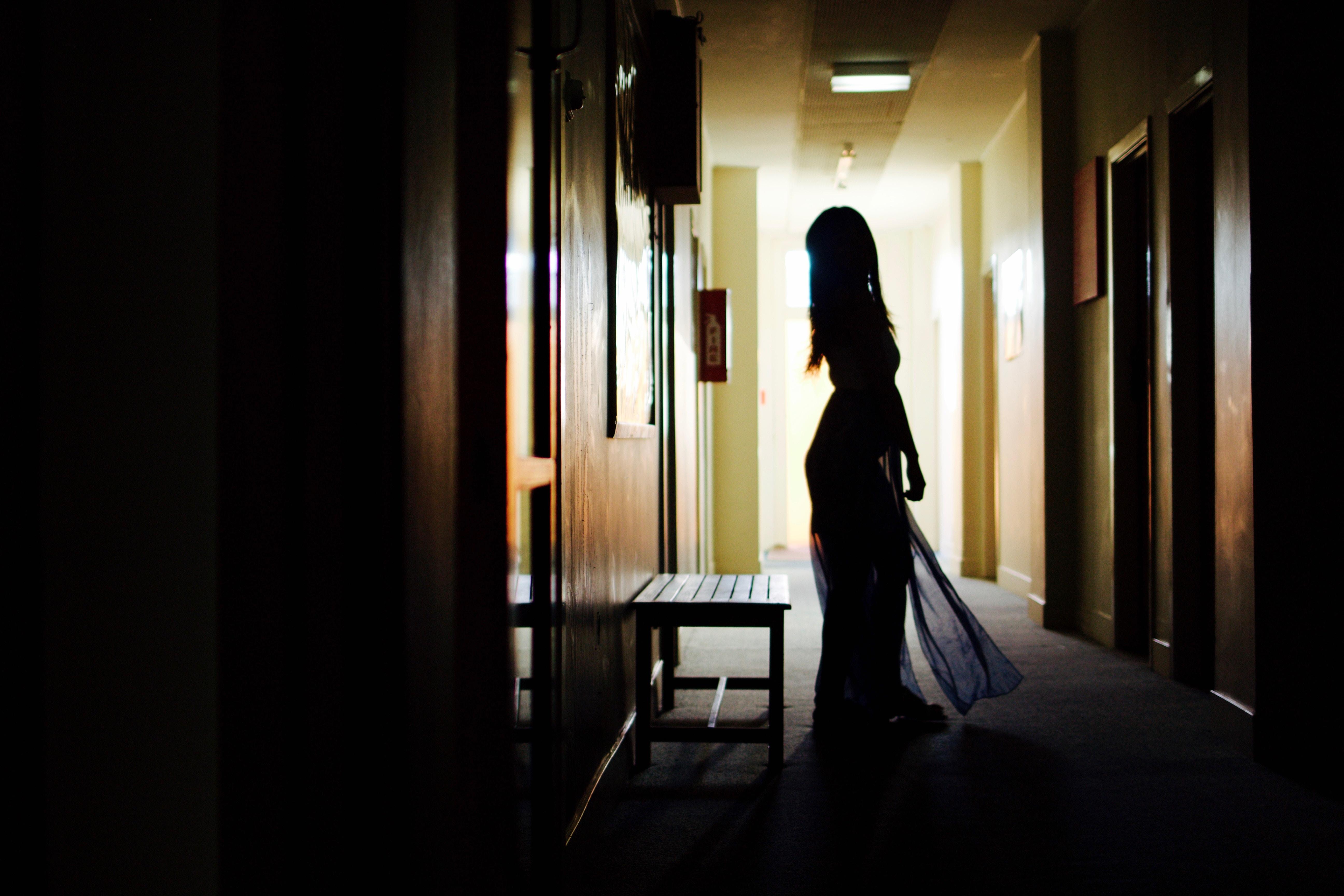 A silhouette of a woman in a dress in a dark corridor