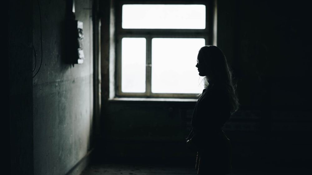 silhouette of woman standing while facing wall inside room