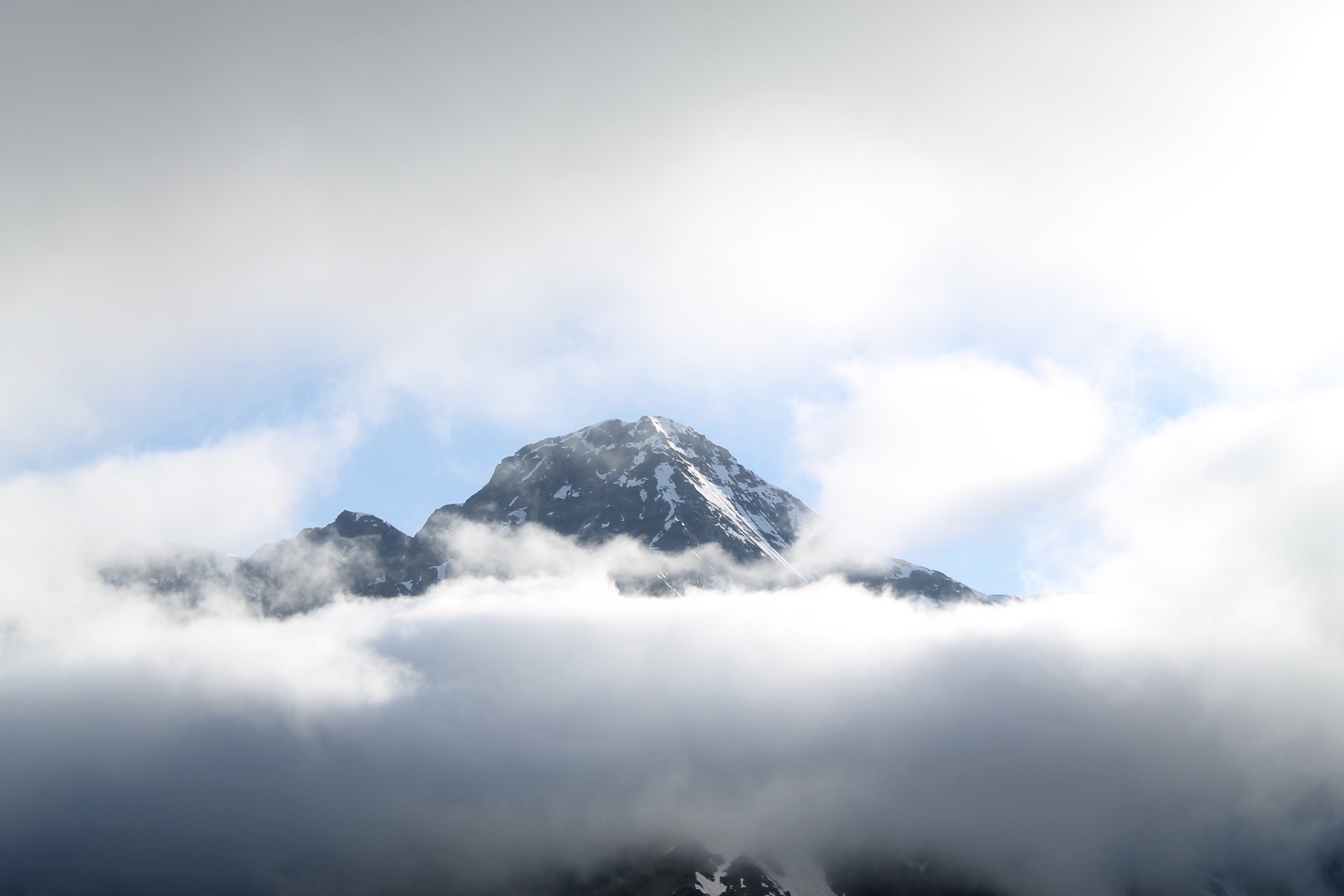 Thick clouds envelop a tall mountain peak, partly obscuring the view