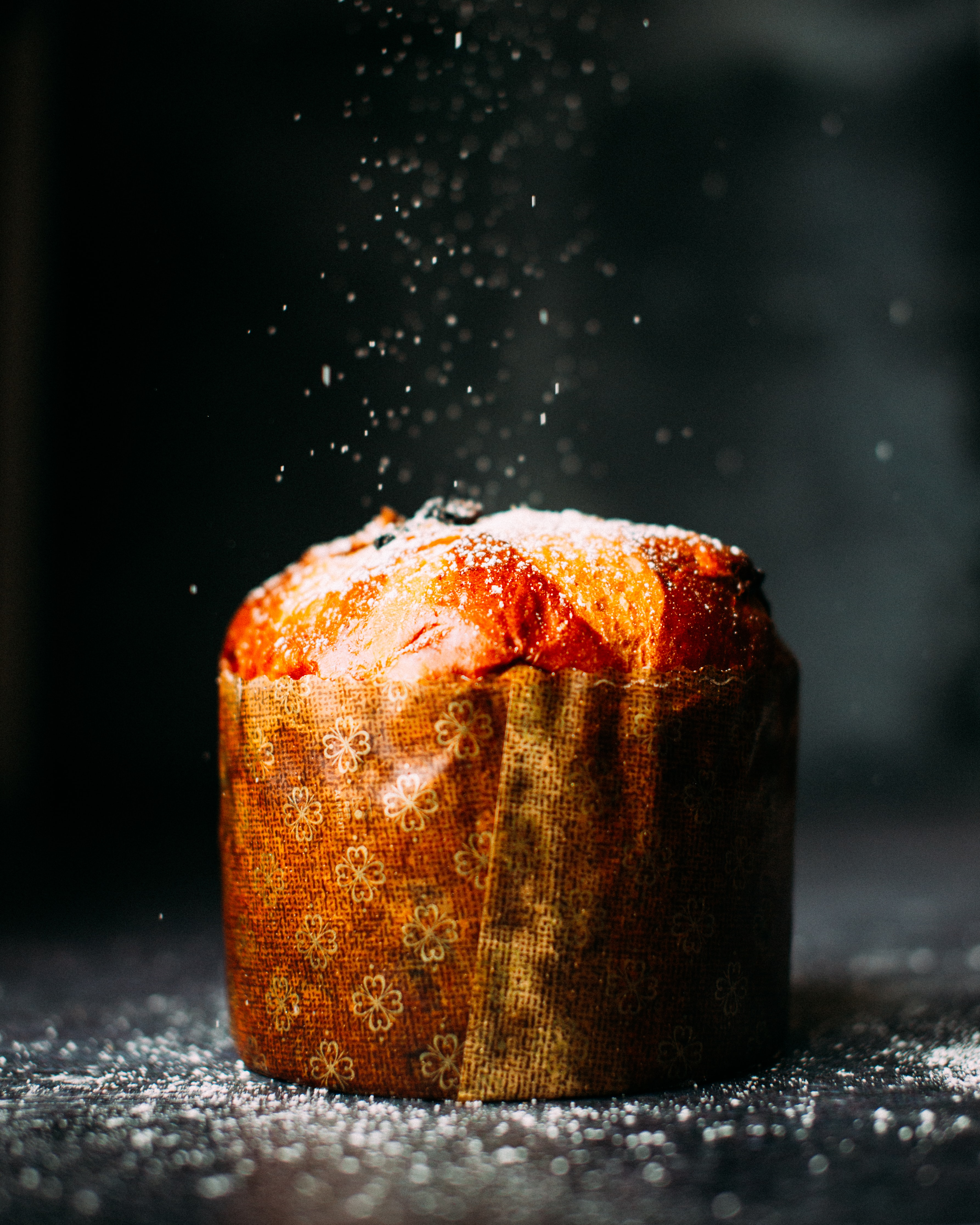 A muffin wrapped in paper and sprinkled with powdered sugar