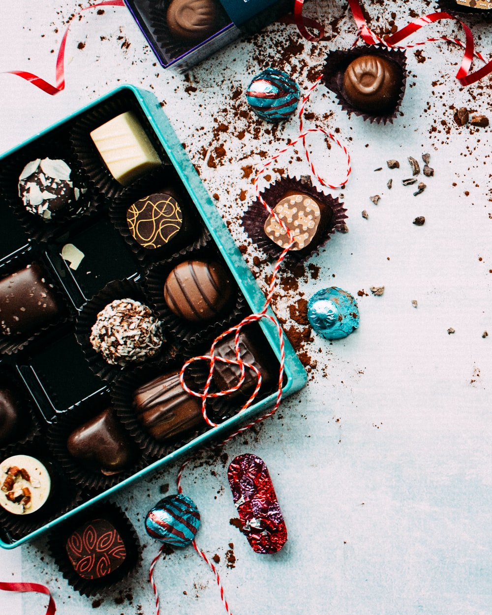 chocolates with box on white surface