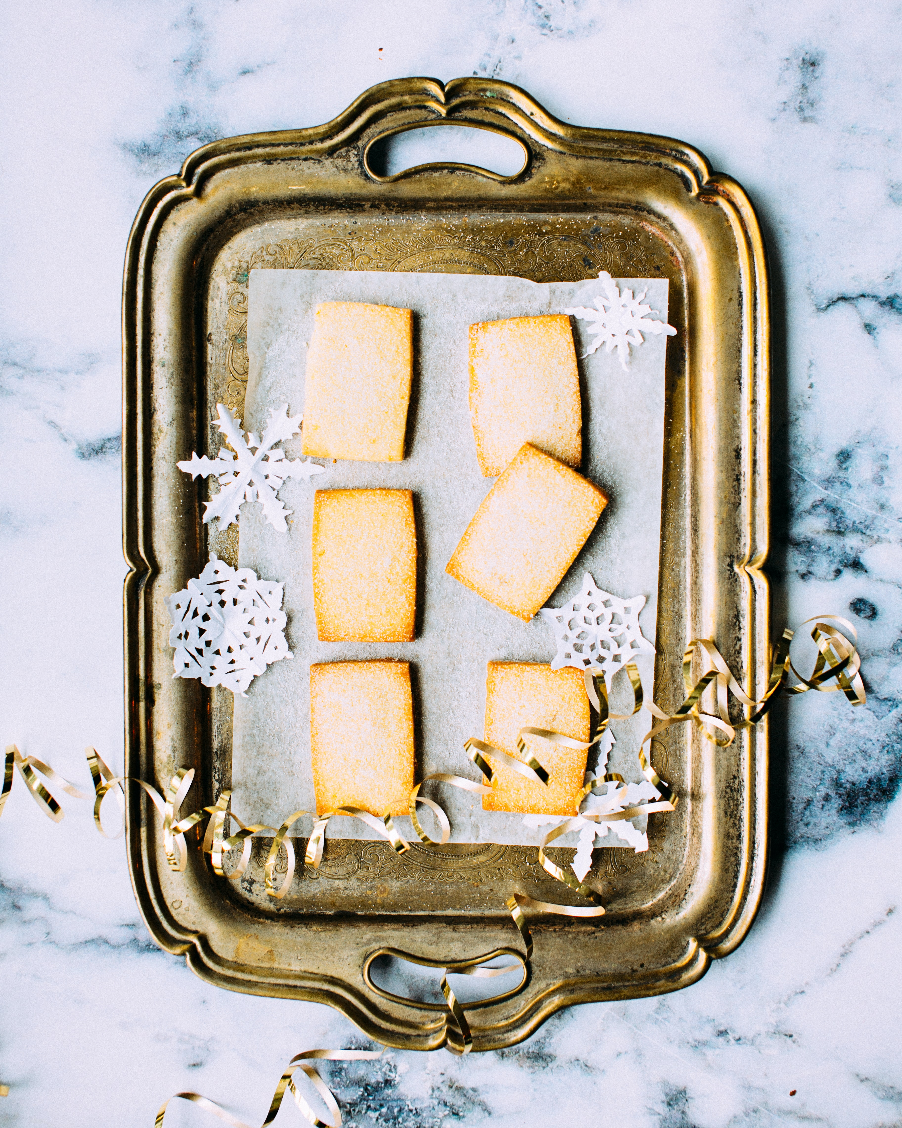 An overhead shot of cookies and paper snowflakes on a golden tray