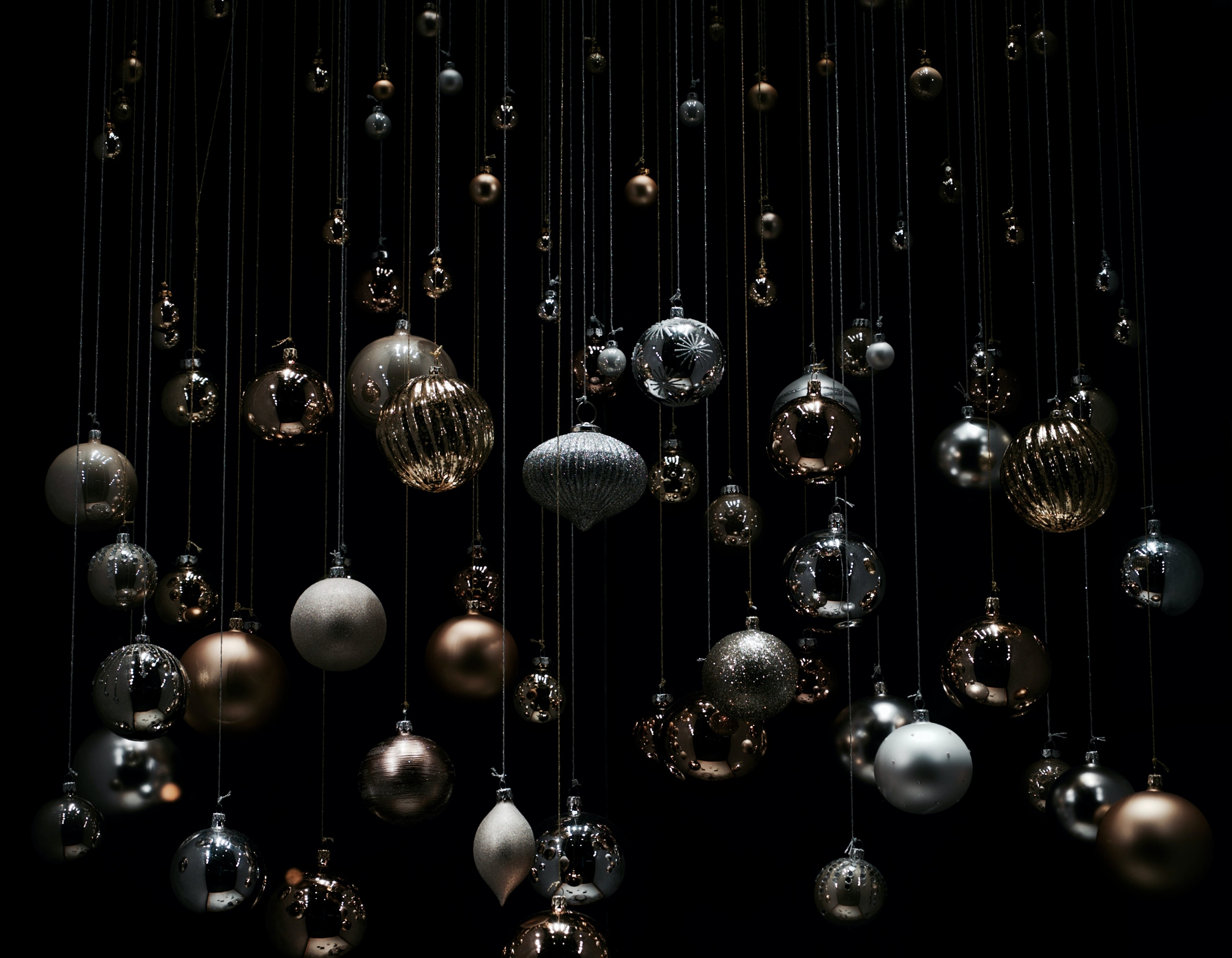 Dangling silver Christmas ornaments surrounded by darkness.