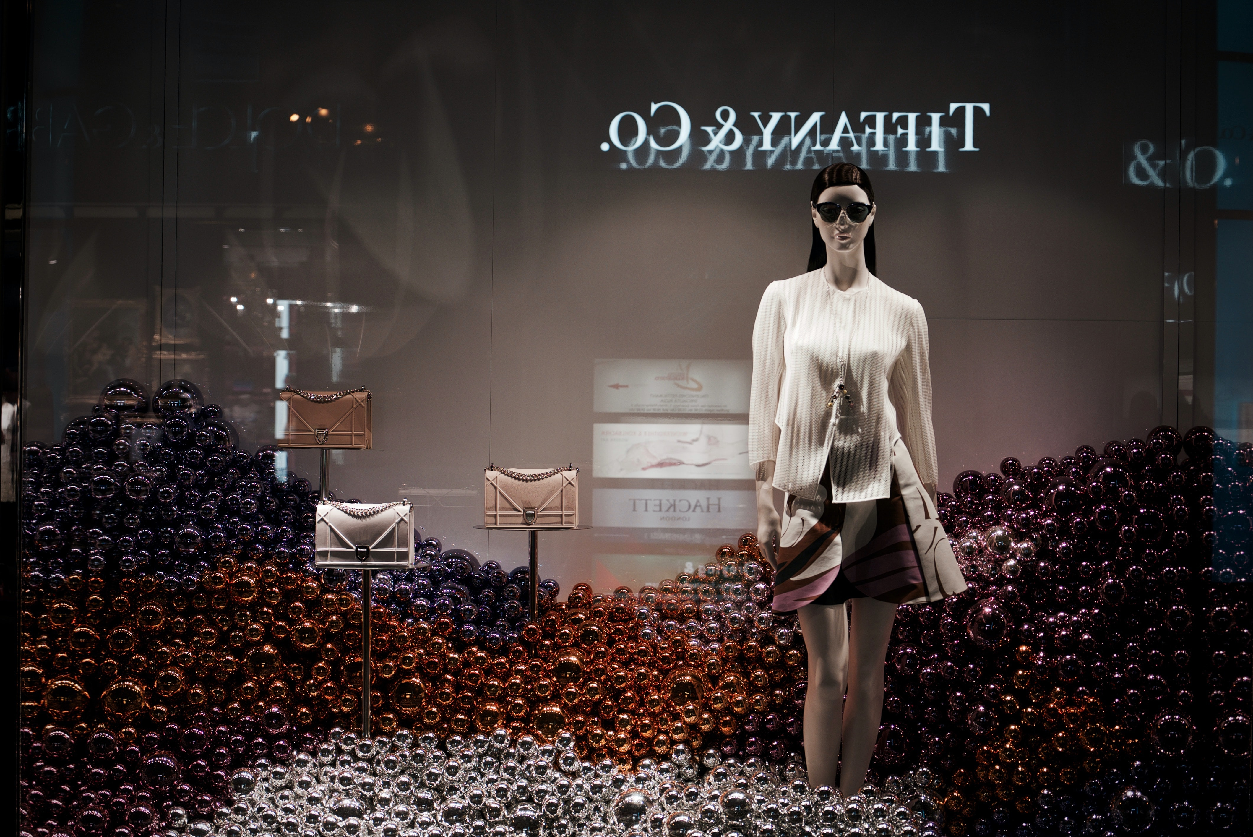 Tiffany an Co Christmas window display with holiday ornaments and a fashionable mannequin