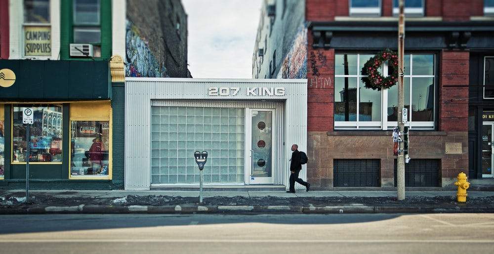 man walking beside 207 King building during daytime