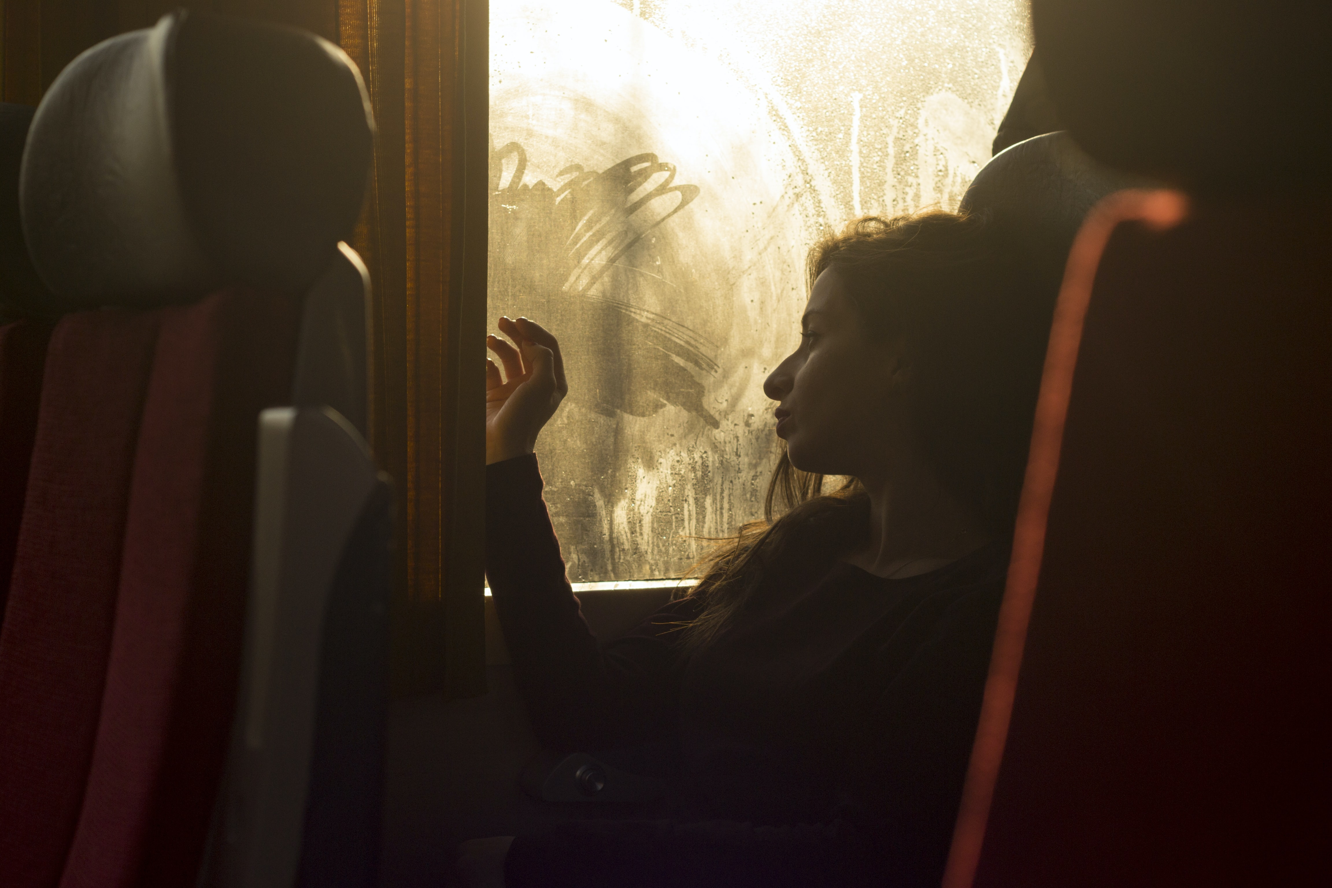 A woman on a bus drawing with her fingers on steamed-up windows