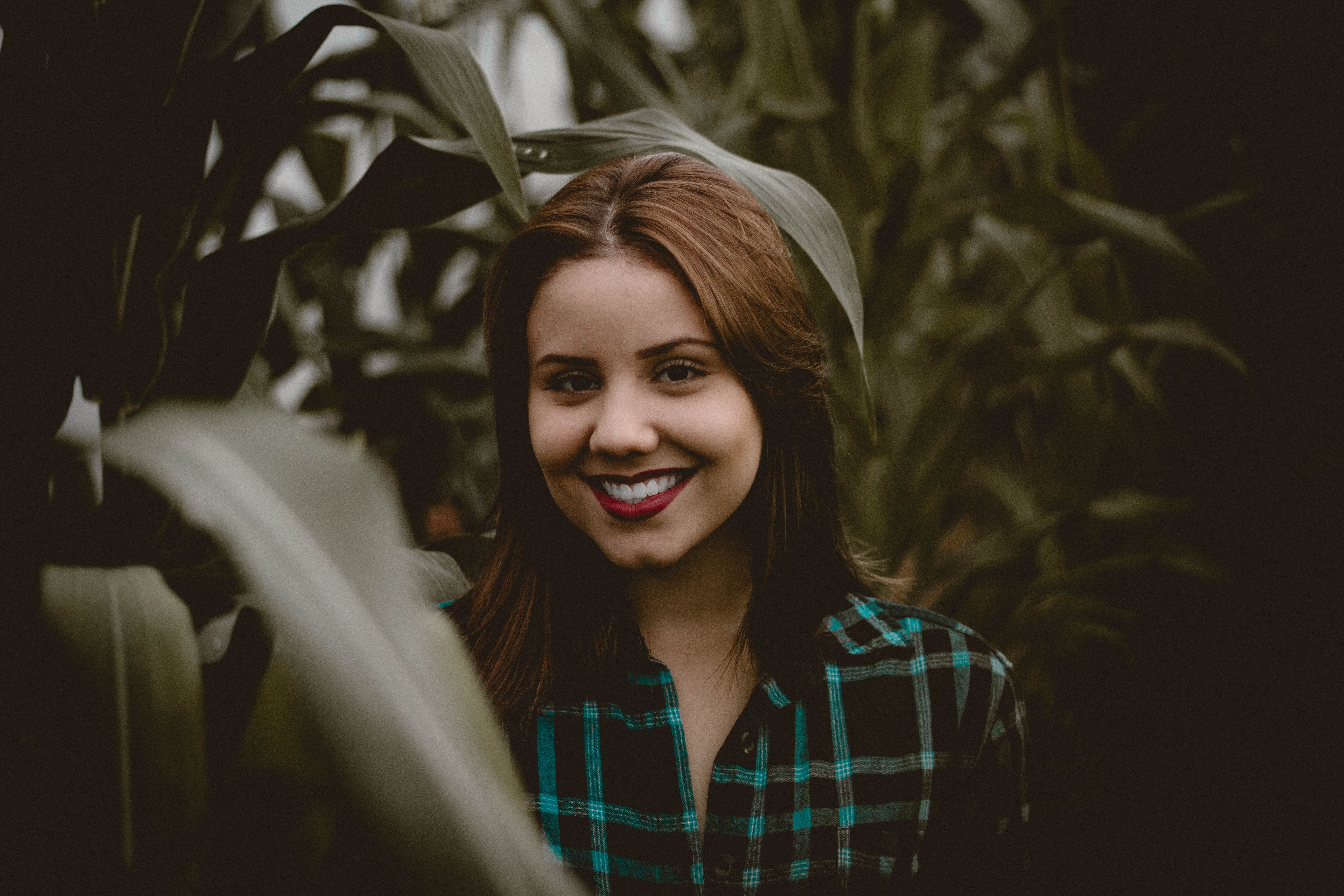 A woman in crimson lipstick and a plaid shirt smiles in a cornfield