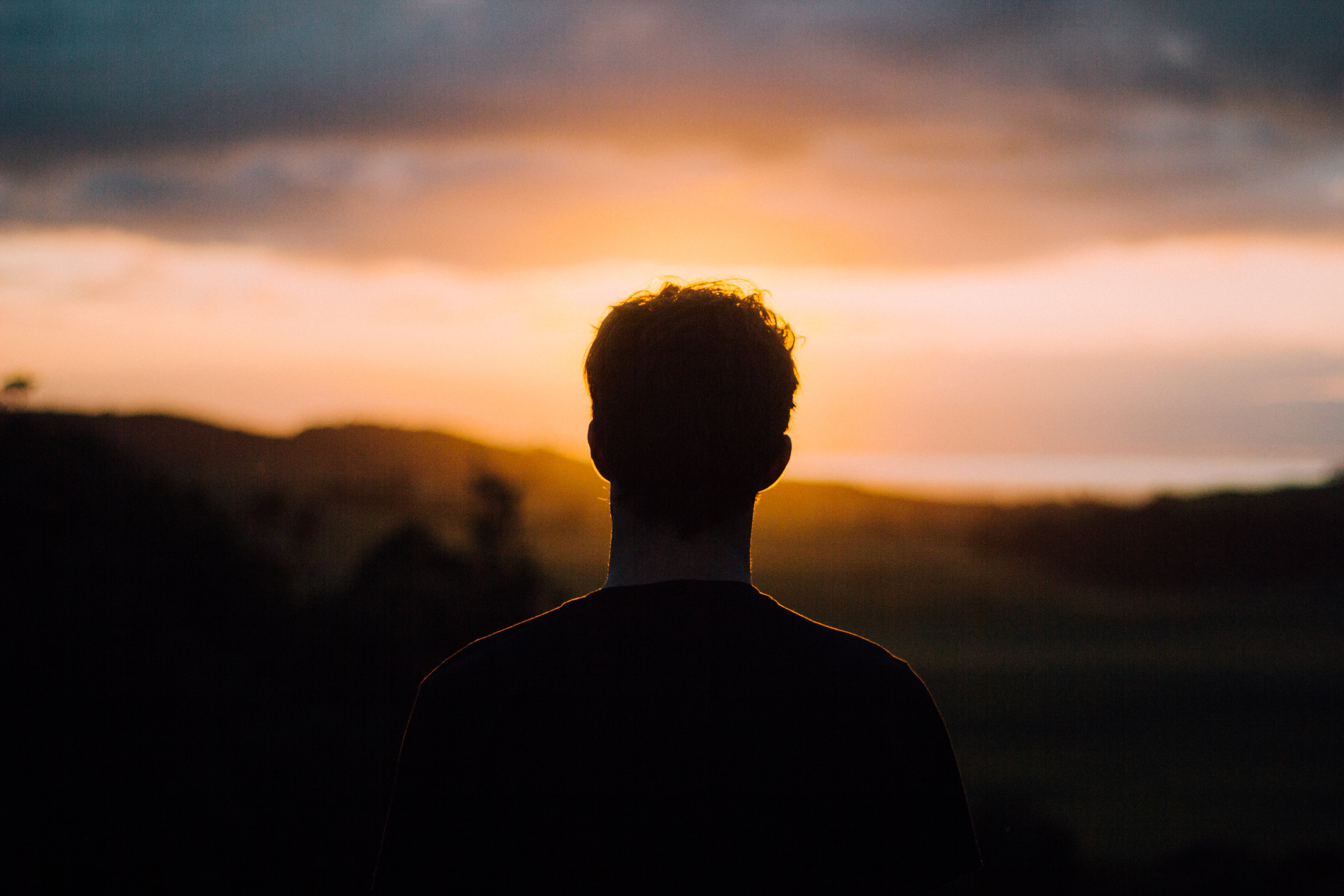 Silhouette of the back of a man's head, looking at the sun in a cloudy, orange sky