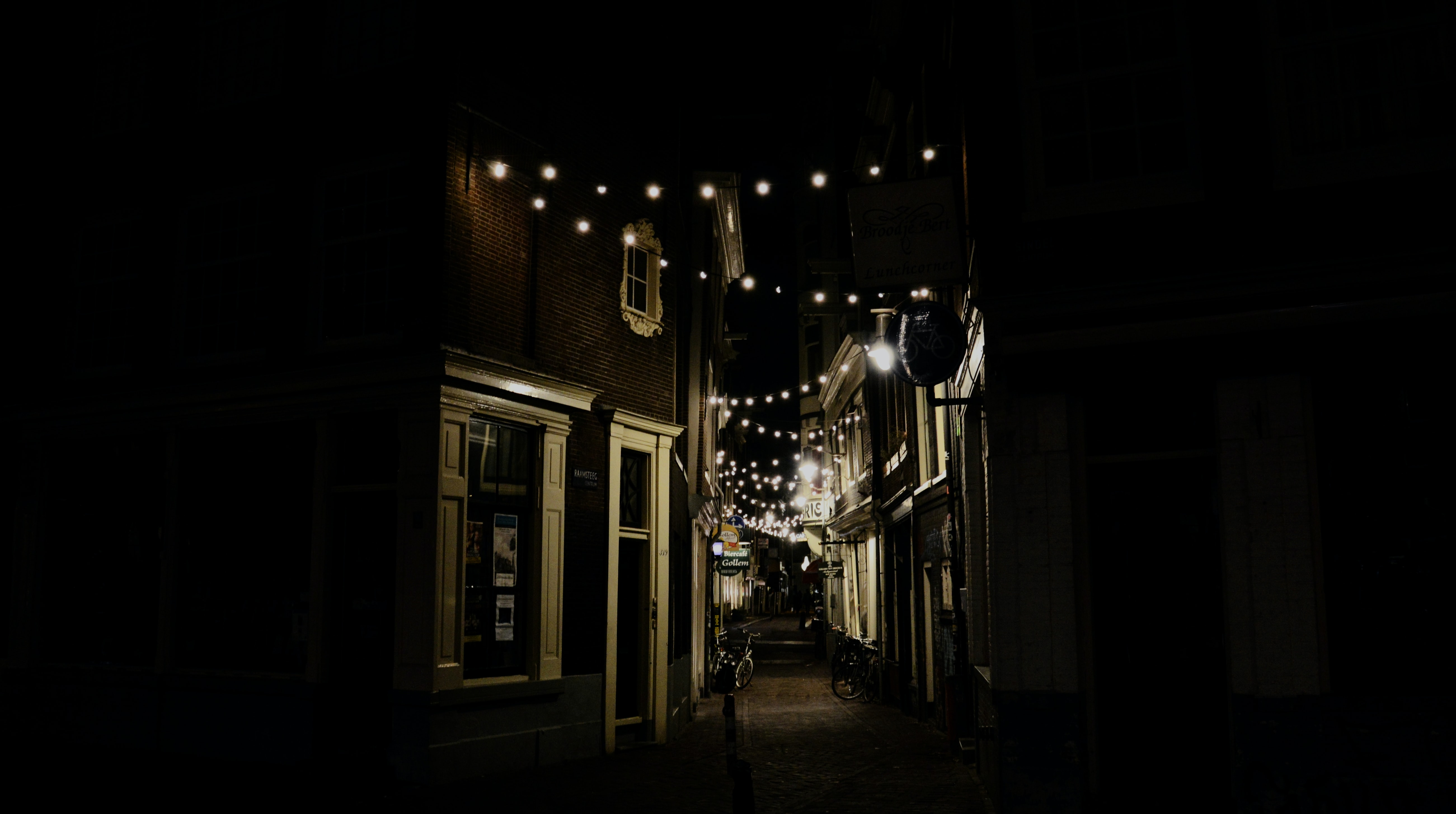 Faint lights in a dark alley in Amsterdam