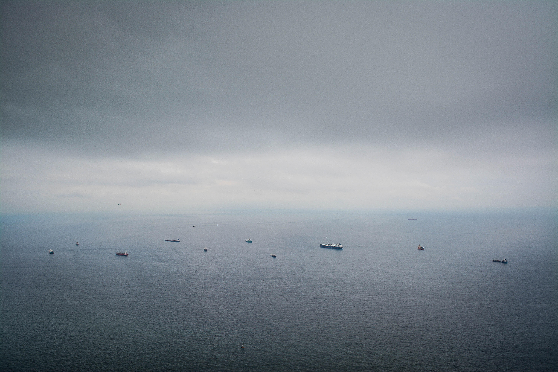boats on calm sea under dim sky