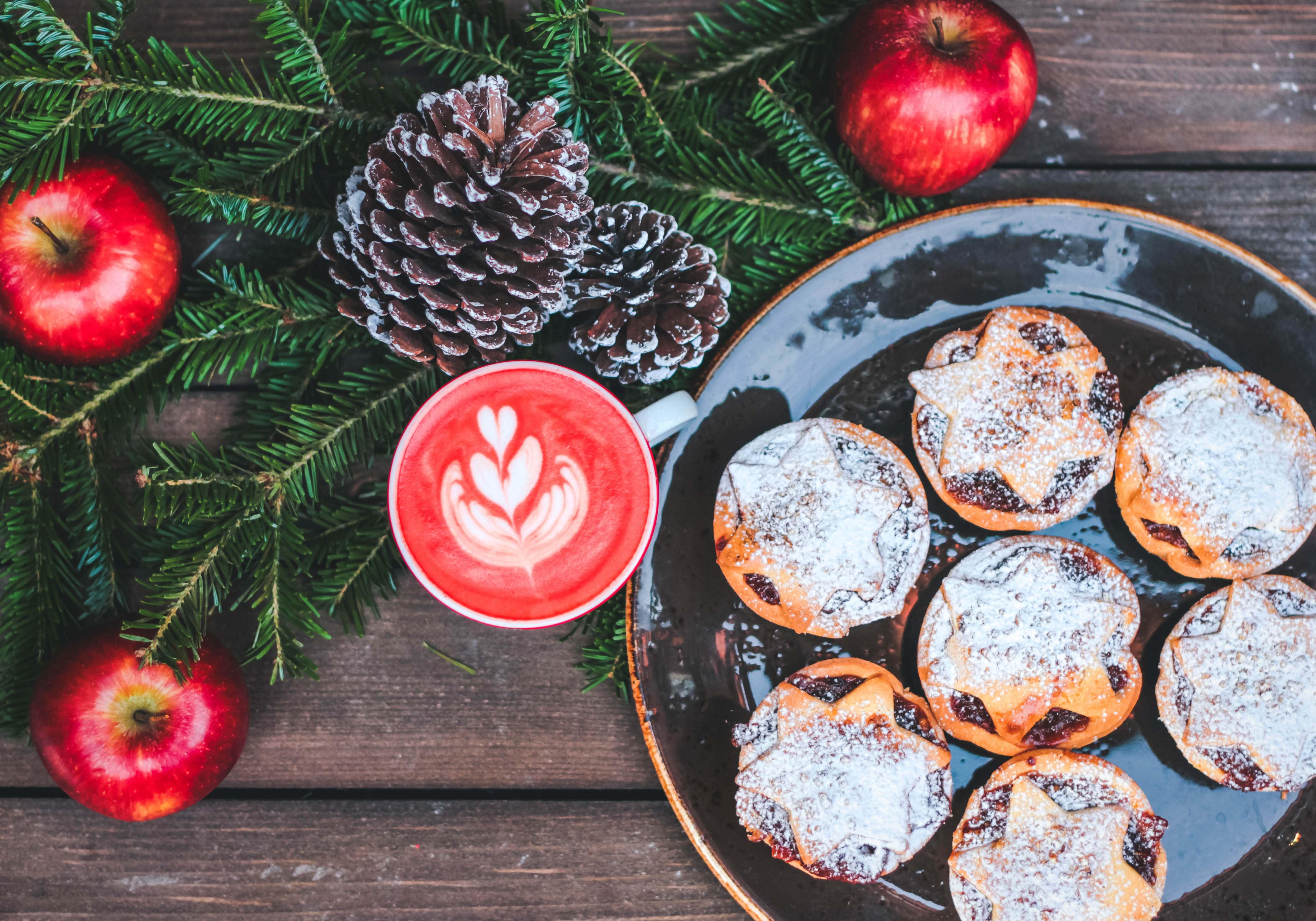 A festive set up of apples, pine leaves, acorns, and mince pies in London