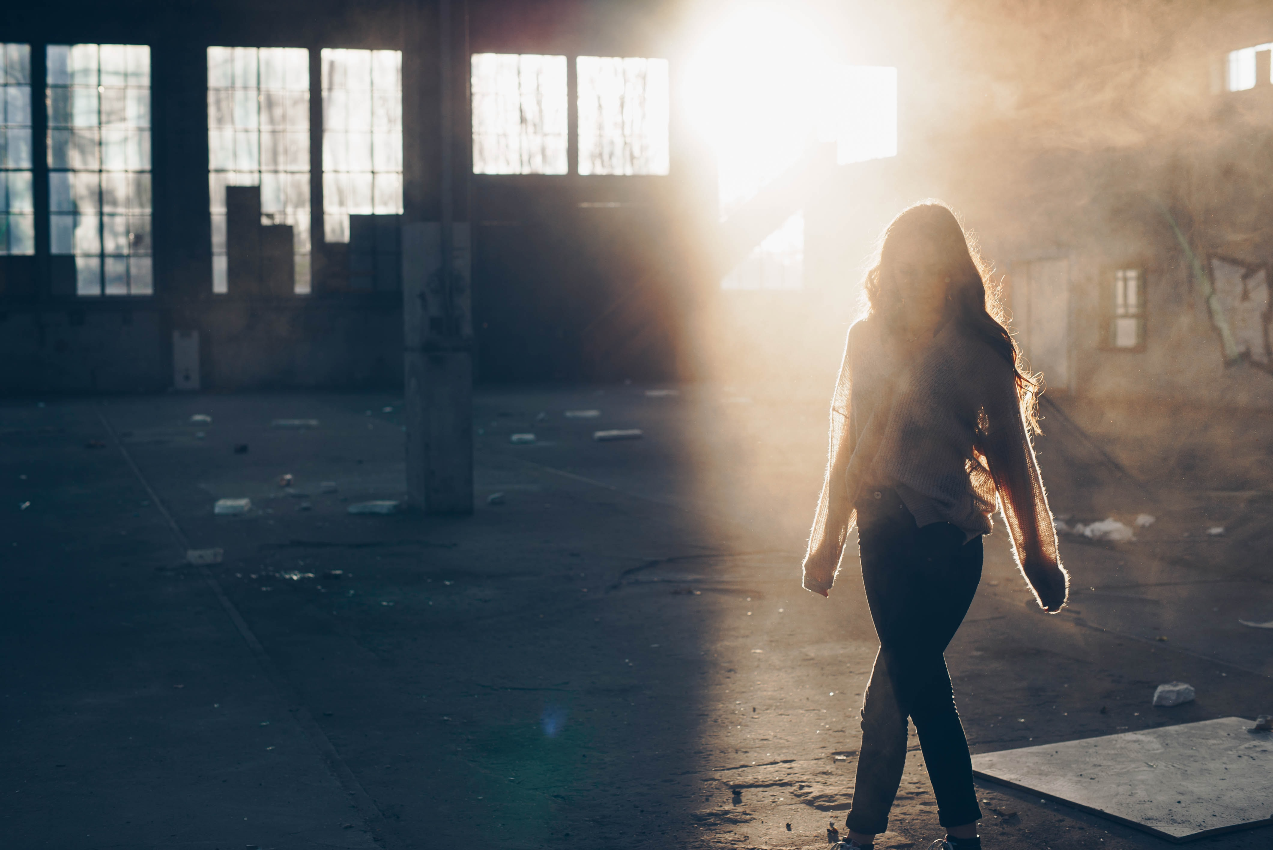 Backlit woman walks through an abandoned foggy warehouse