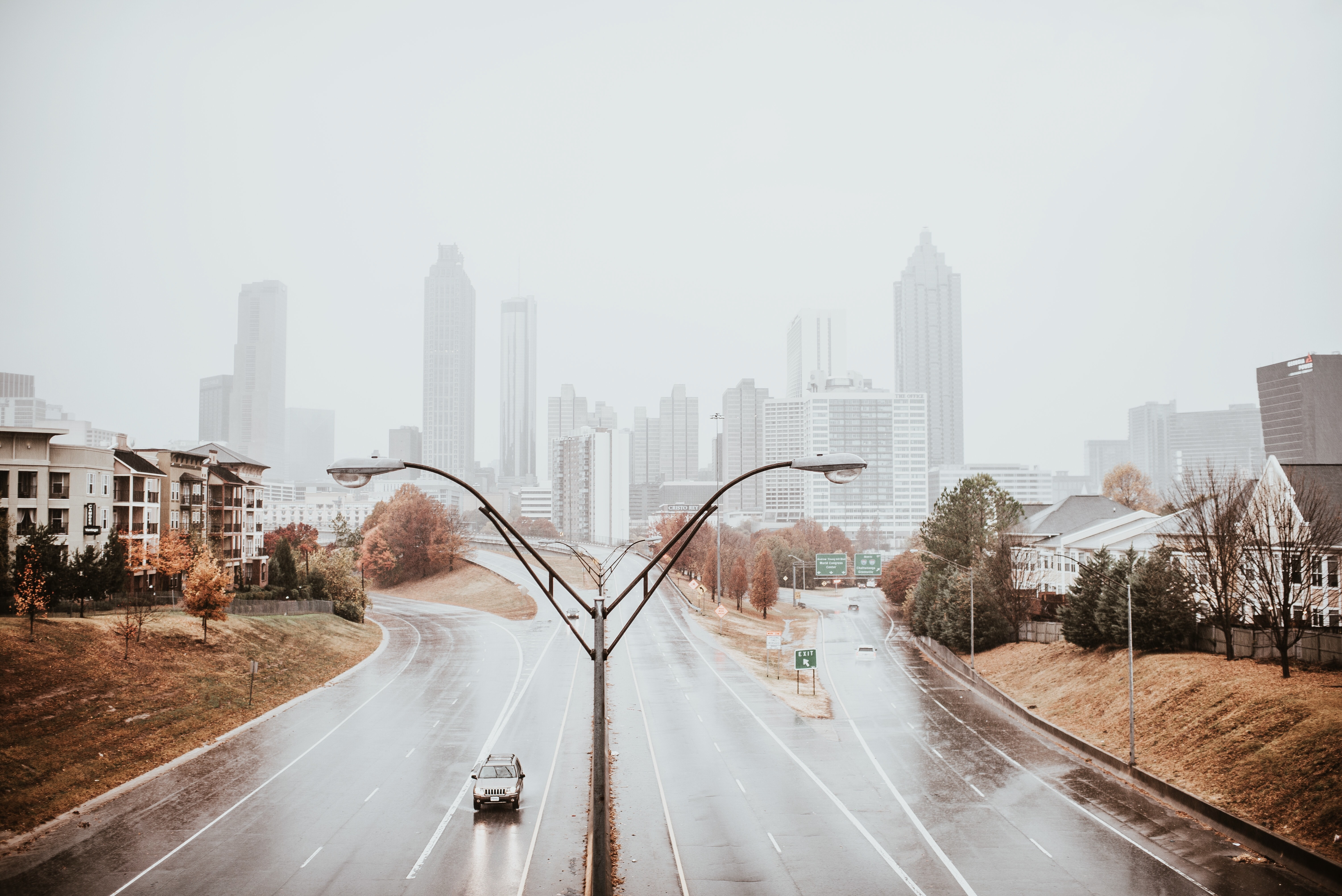 Lone vehicle on a wet highway in Atlanta with fog-covered skyscrapers in the background.