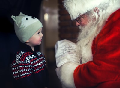 toddler in black sweater standing in front of santa claus santa teams background