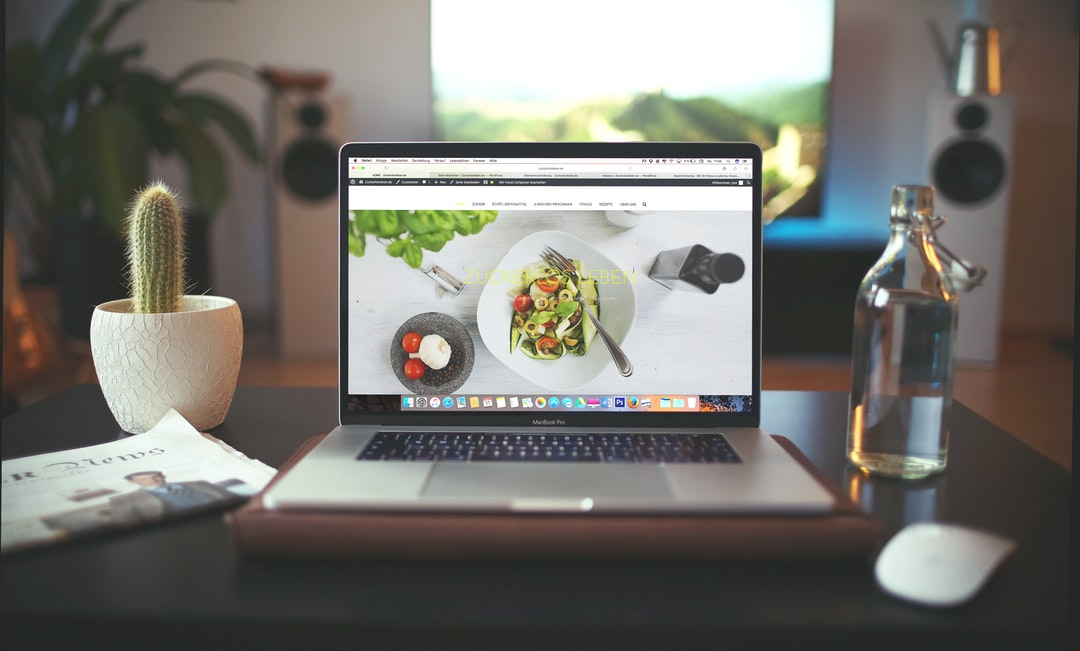 A food blog displayed on the screen of a MacBook on a desk