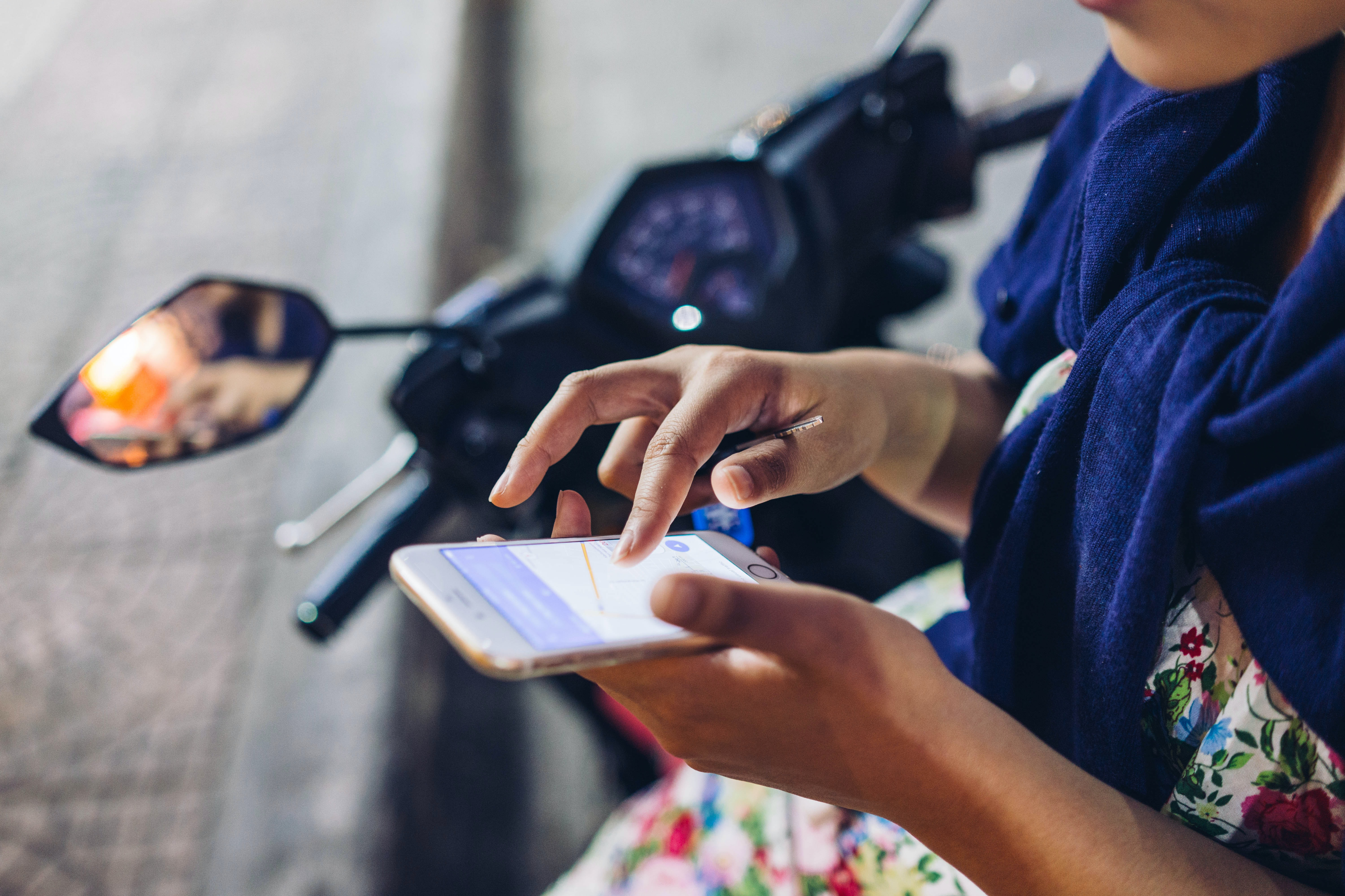 A woman in a floral dress with a blue scarf, sitting on a motor bike looking at Google Maps on her smartphone.
