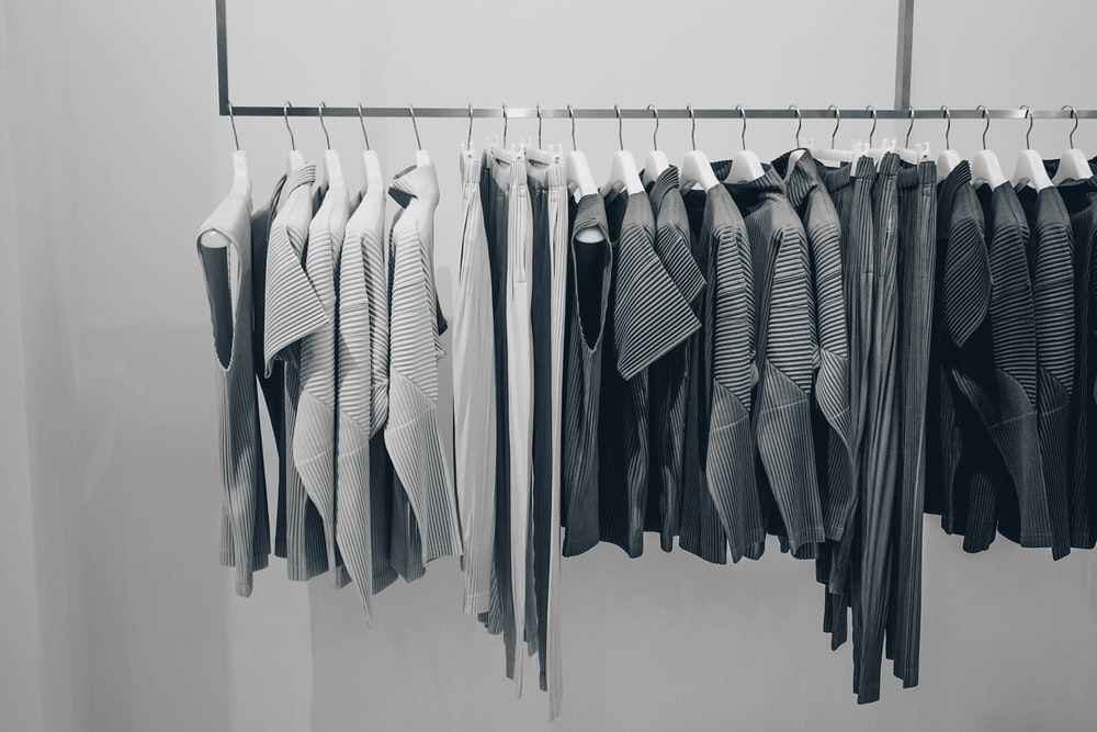 grayscale photo of shirts on rack