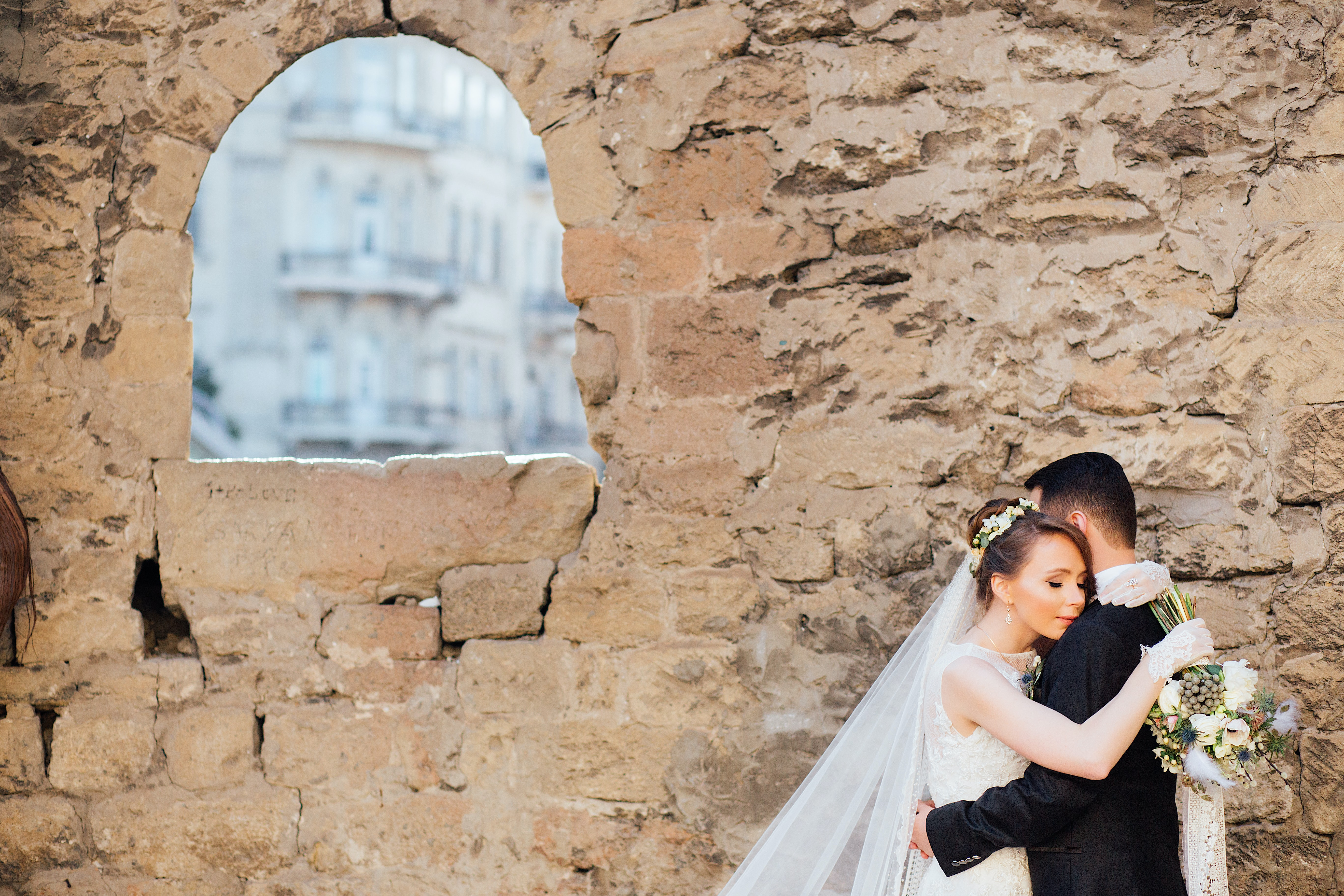A married couple embraces below a window in a stone wall on their wedding day